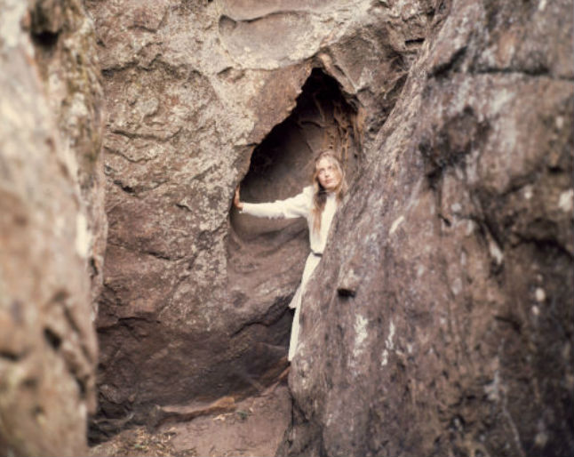 Anne Louise Lambert as Miranda, wearing a white dress and looking up through a gap in the rock in a scene from Picnic at Hanging Rock.