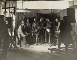 A group of actors stand on a set. There is a camera man in the foreground with a large old-fashioned camera. A woman is directing the action. You can only just make out her silloughette because she is in a long black dress with a short black bob.