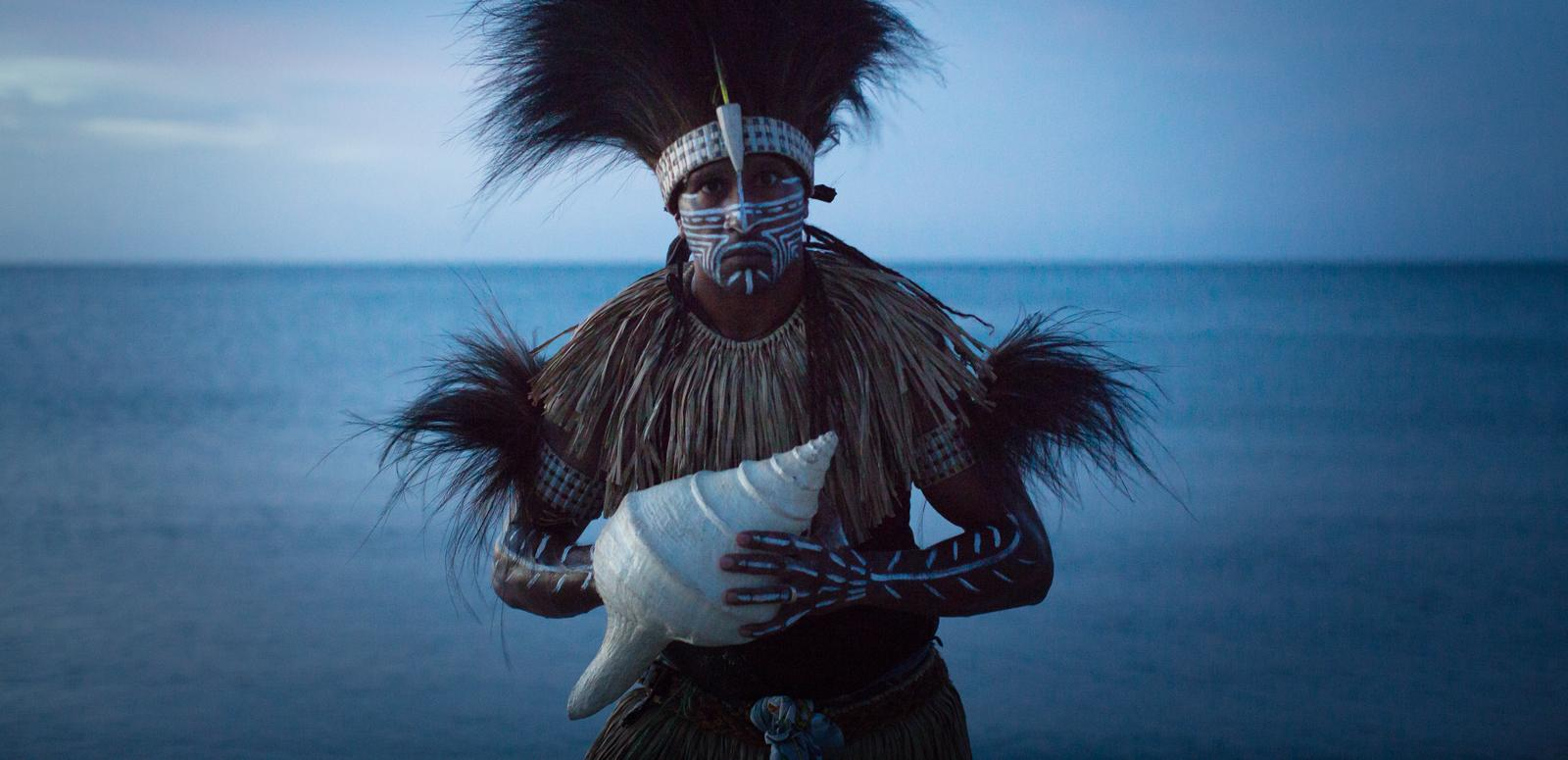 Image featuring Indigenous Francis Williams of the Naygayiw Gigi Dance Troupe in costume standing in front of the sea
