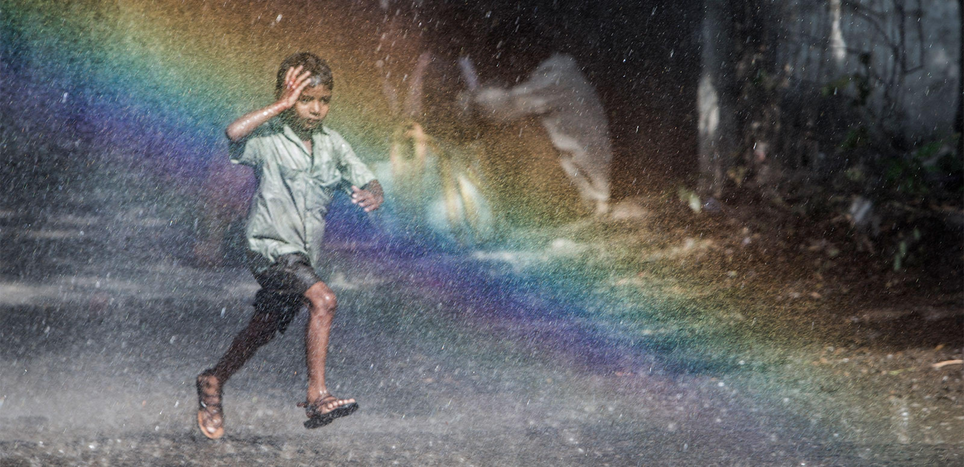 A young Indian boy runs along a street in the rain through a rainbow.