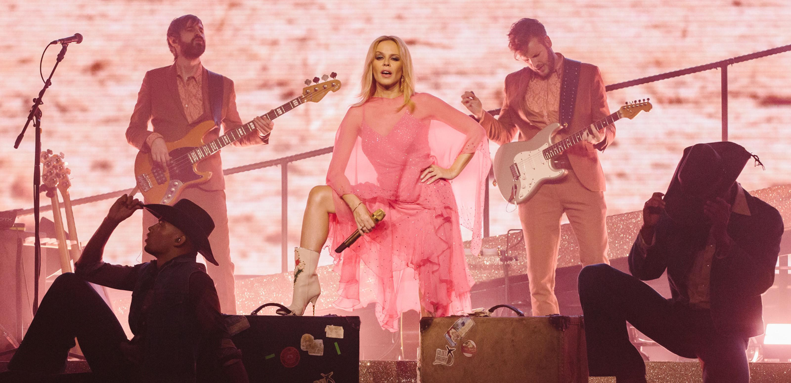 Kylie Minogue is standing on a stage with a foot up on an amplifier in a power pose. There are dancers in front of her and two musicians on stage with her playing guitar.