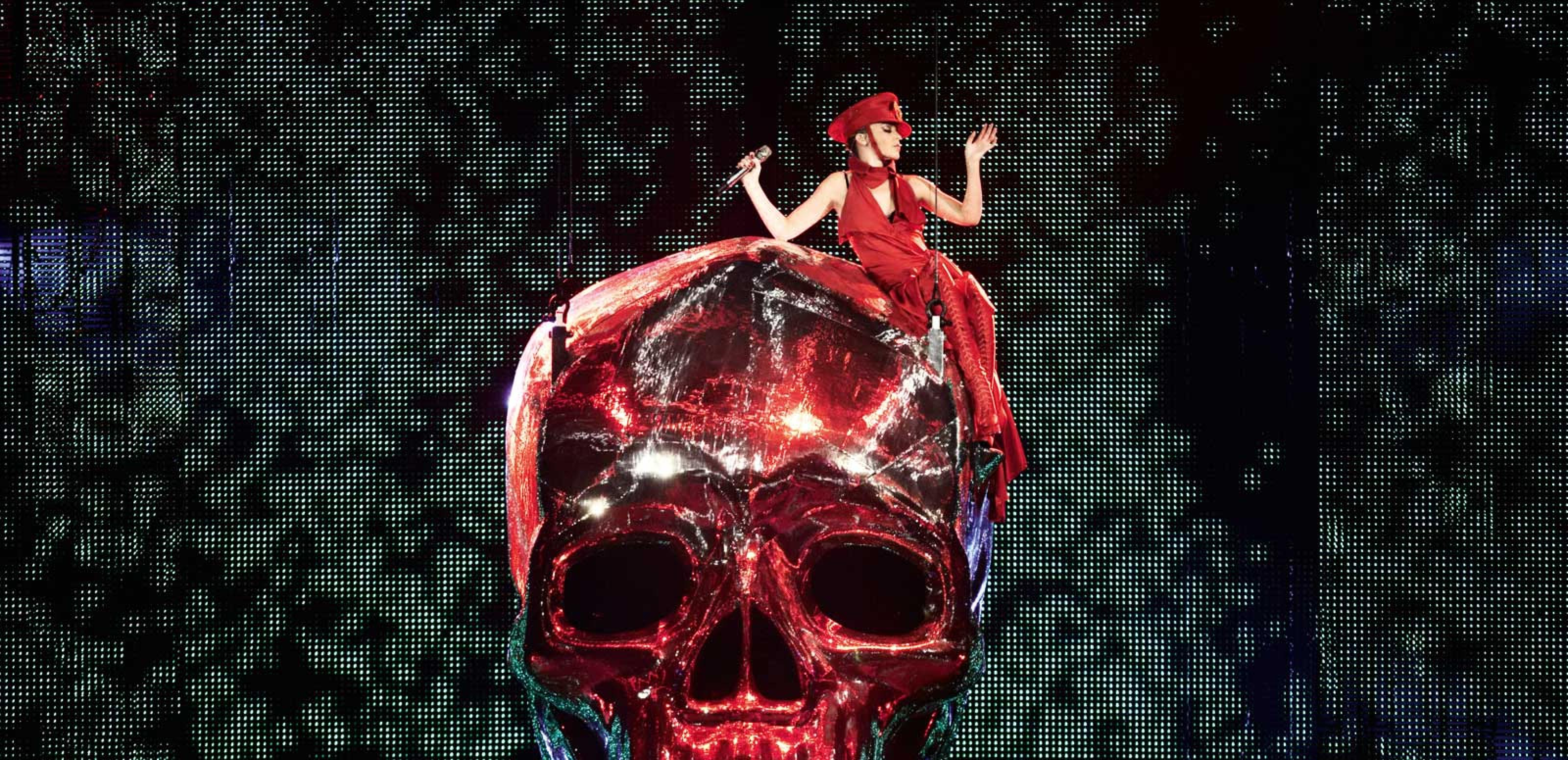 Kylie Minogue, dressed entirely in red, is sitting on top of a giant red shiny skull prop at one of her live shows.
