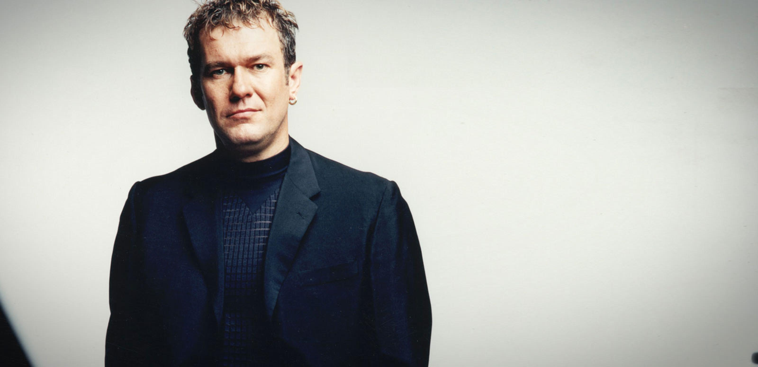 Jimmy Barnes wearing a black suit and shirt and looking directly at camera. Photographed from waist up.