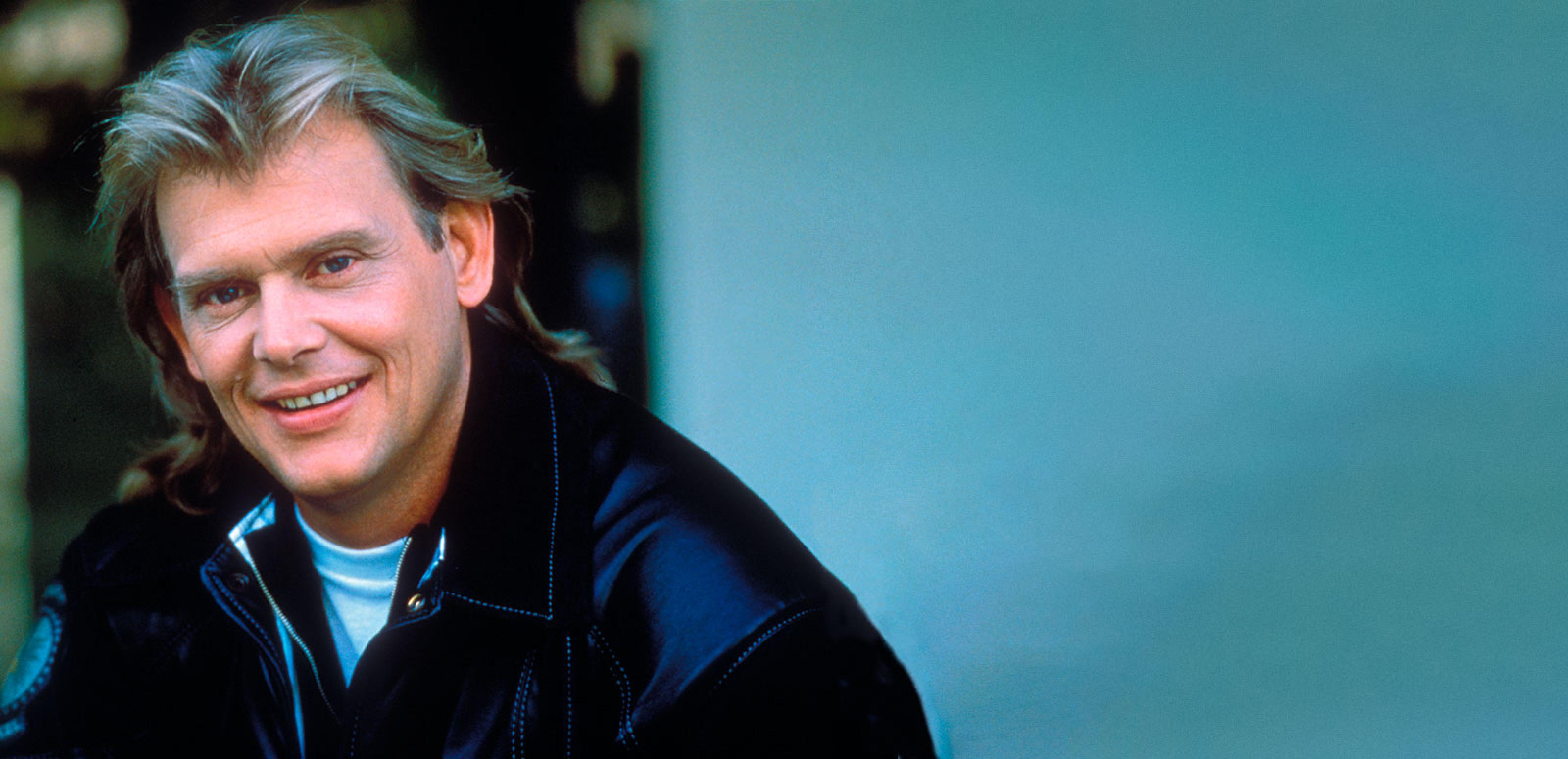 Singer John Farnham, circa late 1980s wearing a black jacket, pictured from the shoulders up. He has his head tilted slightly towards the camera and is smiling.