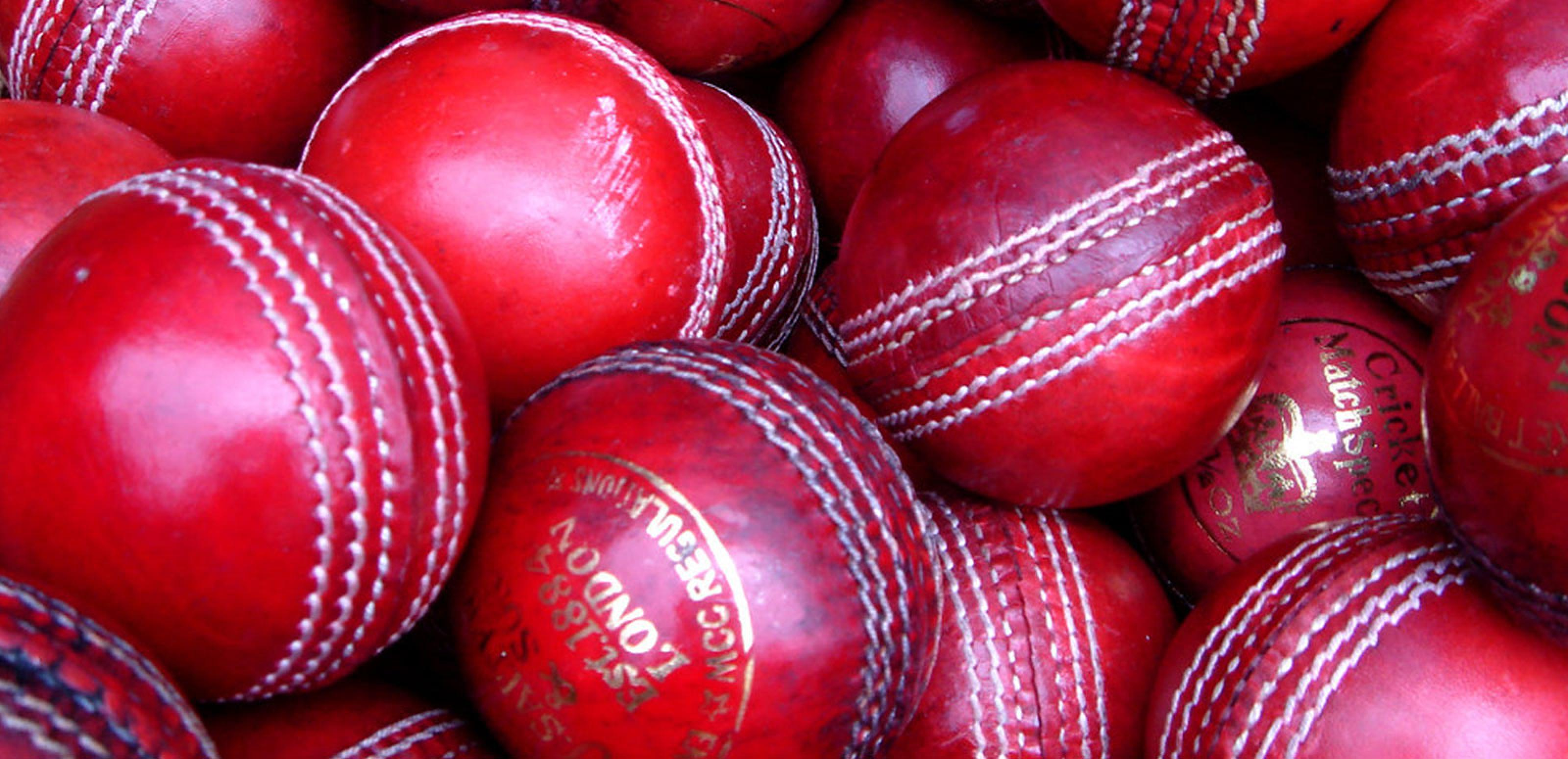 A close up of a collection of new and used red cricket balls inside a basket.
