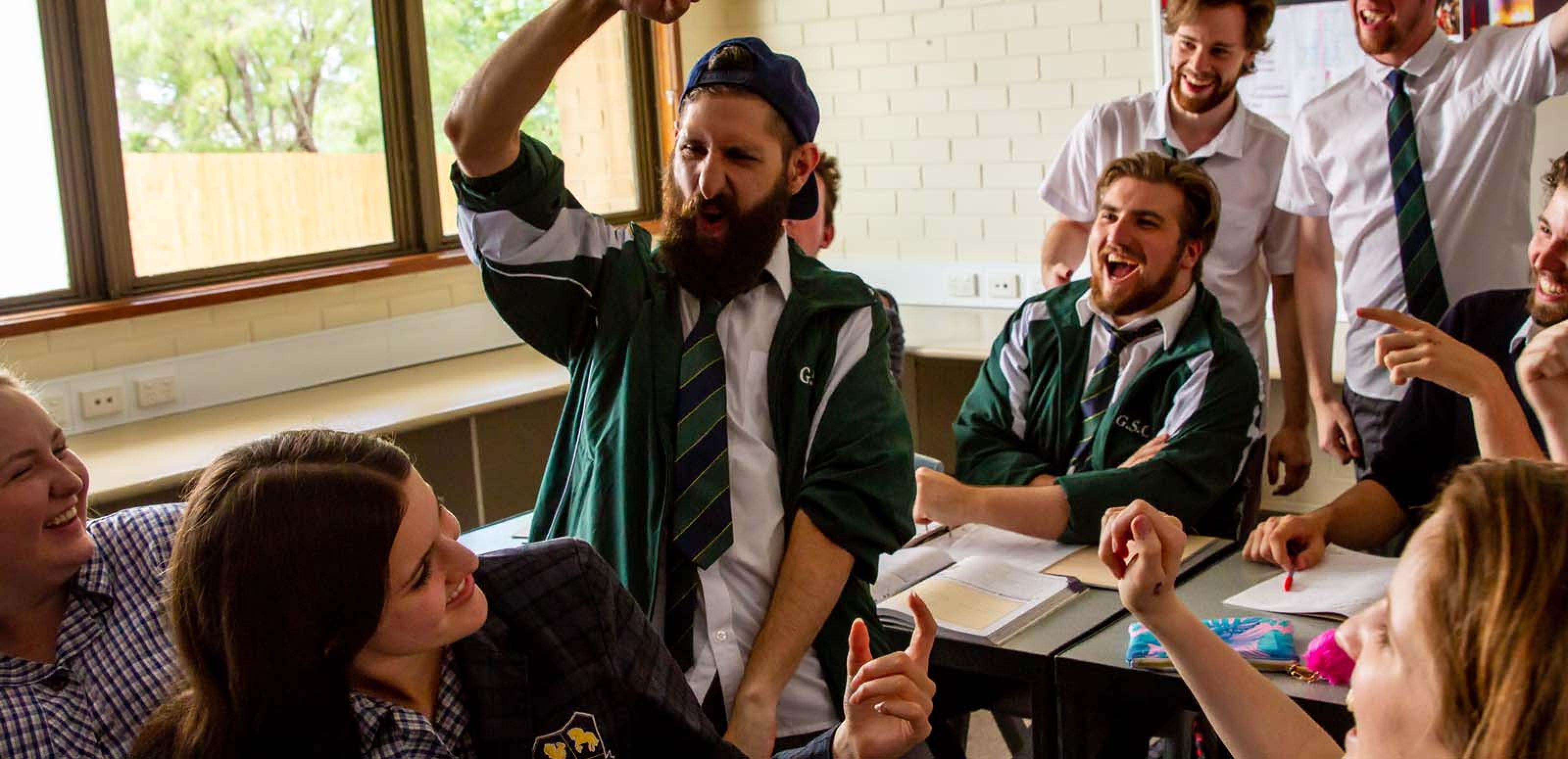 A group of high school students in uniform (including an older man with a beard) laughing and gesticulating