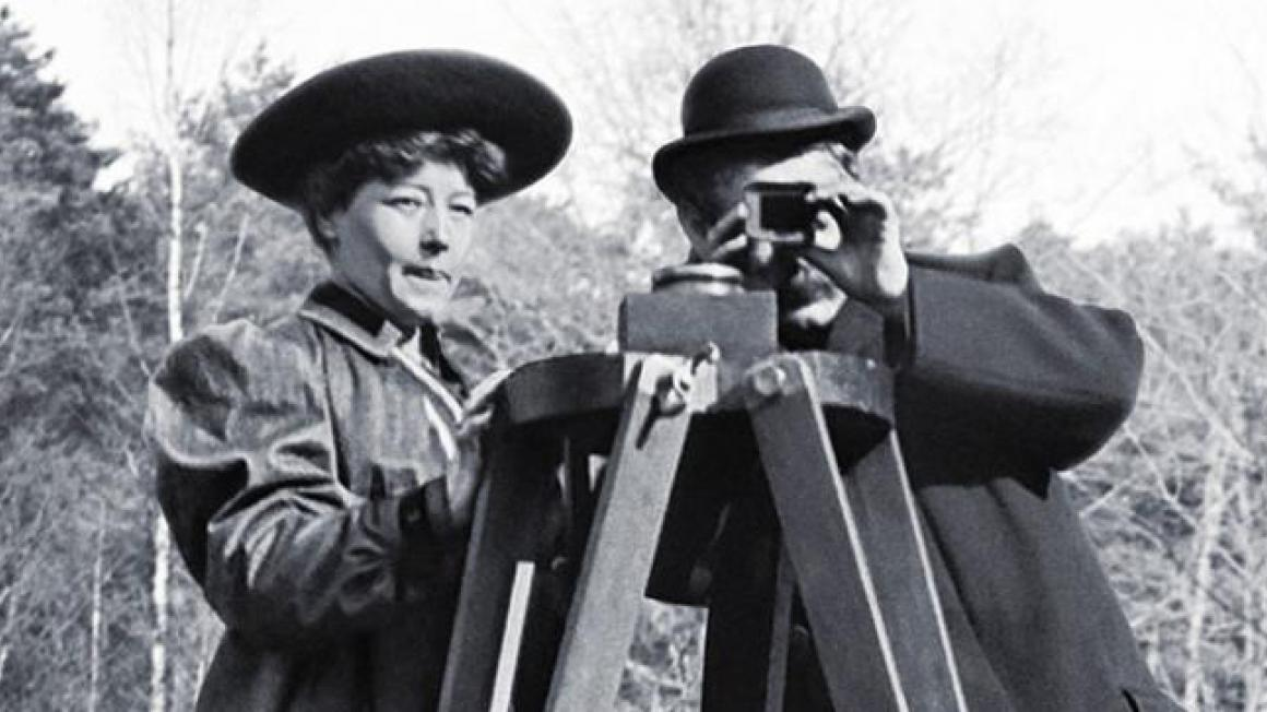 Archival photo of a woman wearing period dress standing next to a man looking through  camera on a tripod