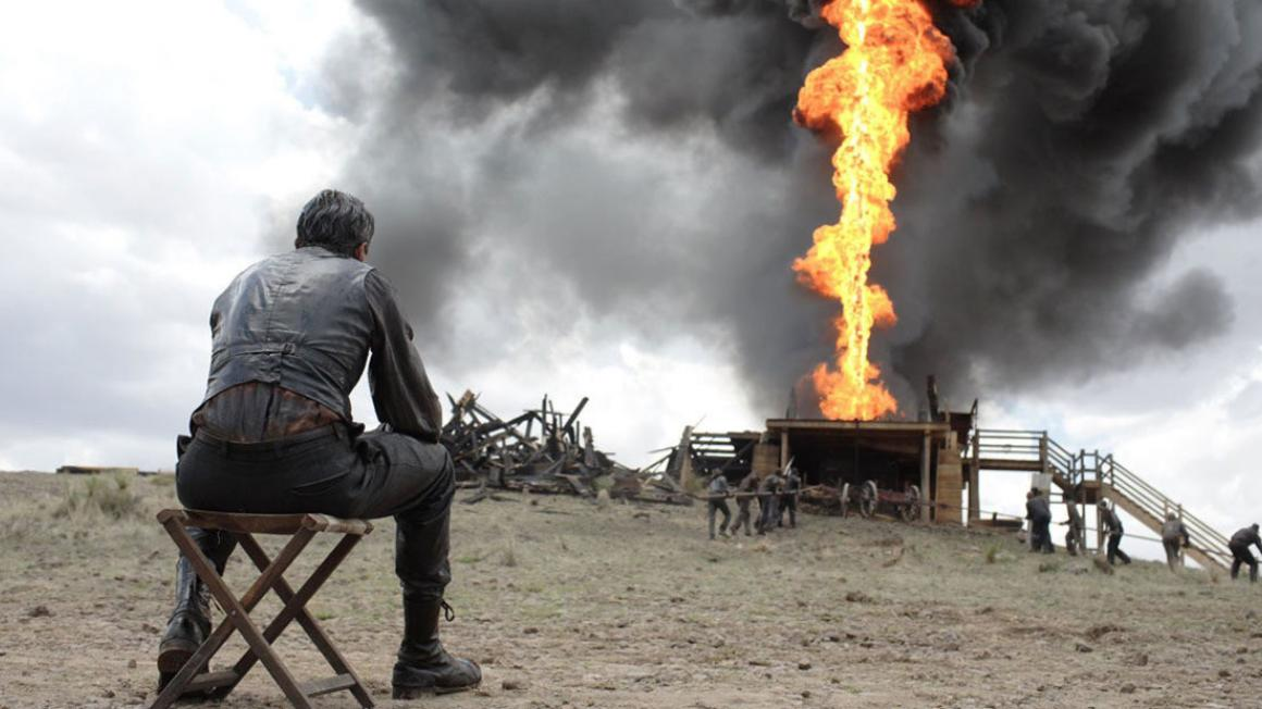A man sits on a stool looking at an oil well on fire.
