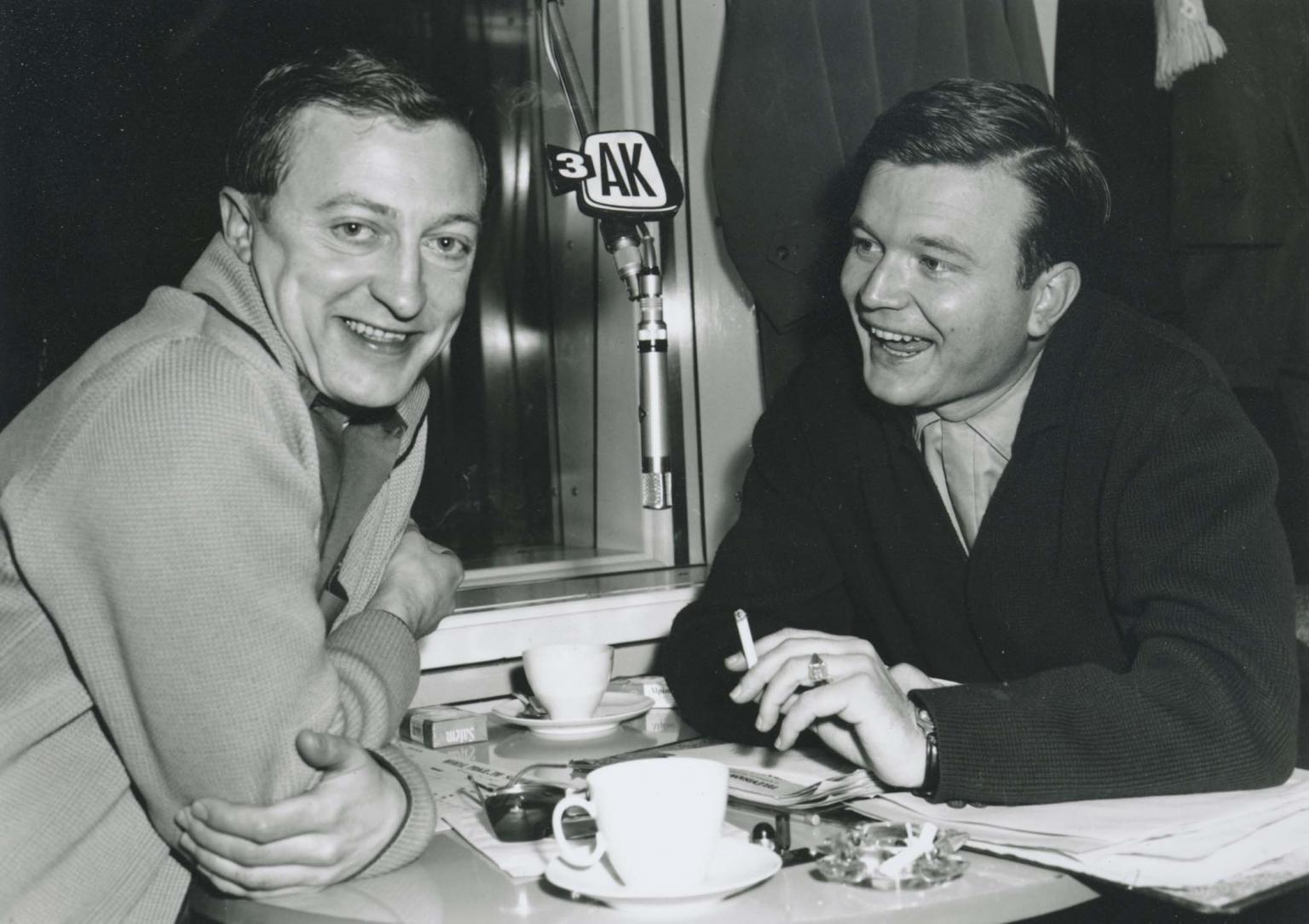 Graham Kennedy smiling to camera sitting opposite Bert Newton in front of a 3AK microphone