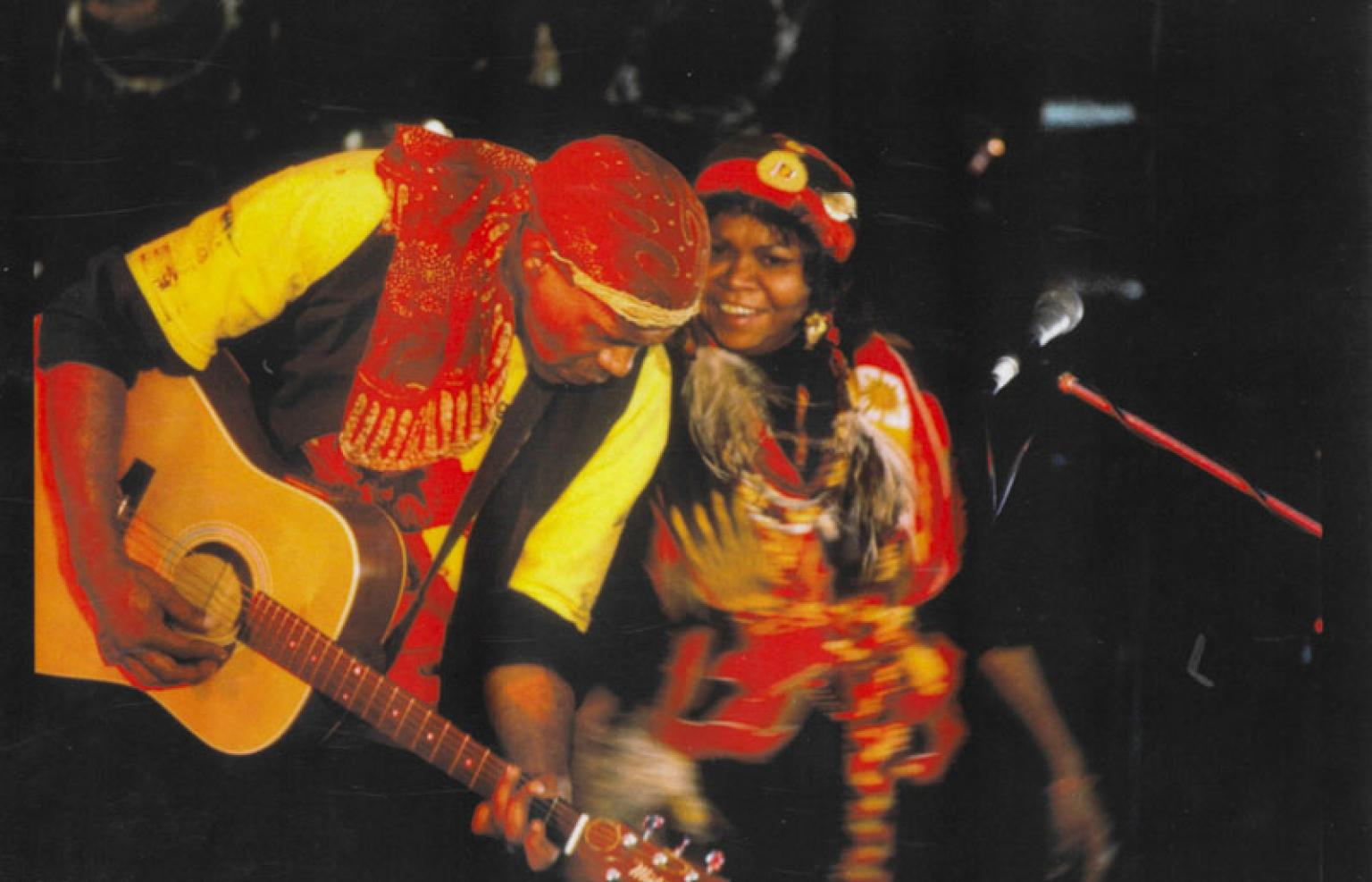 Archie Roach and Ruby Hunter performing on stage together. Archie is playing guitar and Ruby is smiling and they are leaning in towards each other.