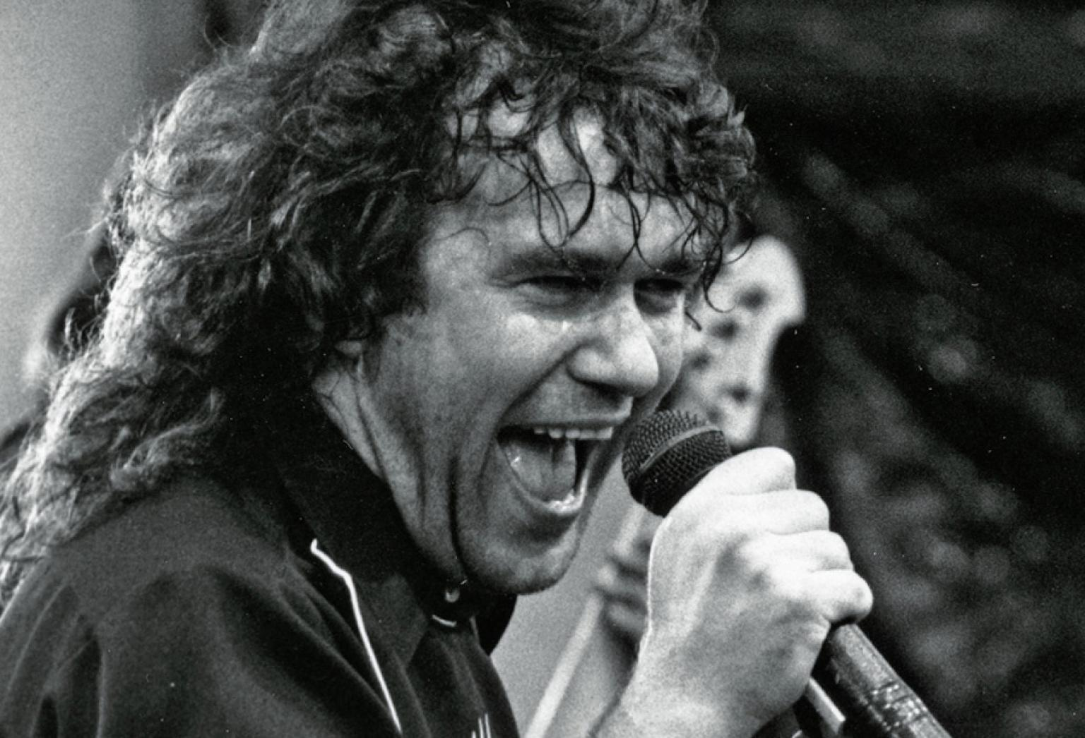 Close up of Jimmy Barnes singing into a microphone on stage.
