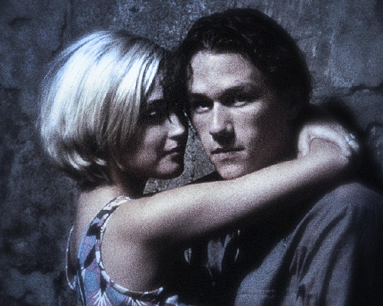 Heath Ledger as Jimmy and Rose Byrne as Alex in a still from Two Hands. The shot is grainy and plays with focus. They are in an embrace while they lean on a wall. Ledger looks at the camera.