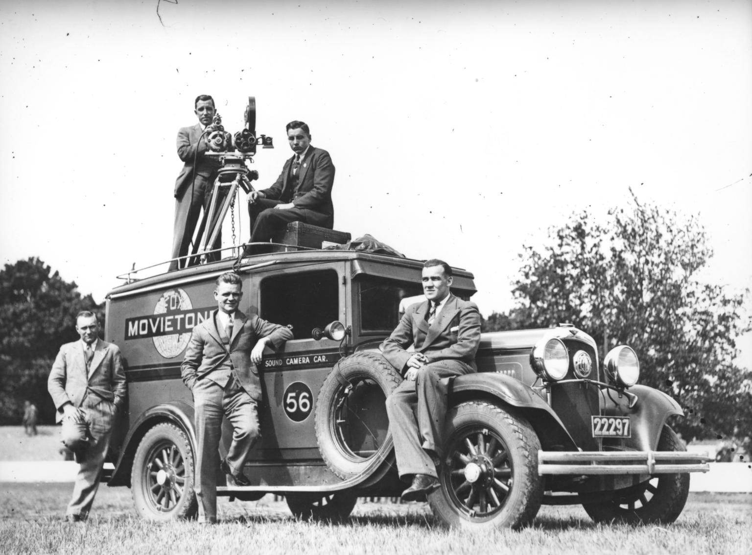 Bill Trerise with a camera on a tripod and one other man on top of Movietone Sound camera car 56, with three other men on the ground.
