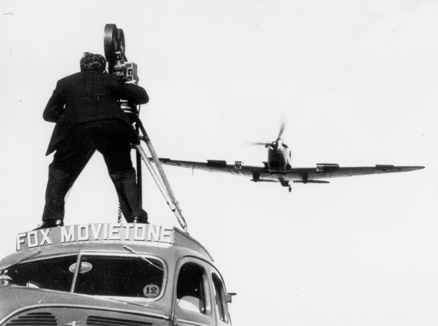 Fox Movietone cameraman standing on a car filming a fighter aircraft flying overhead