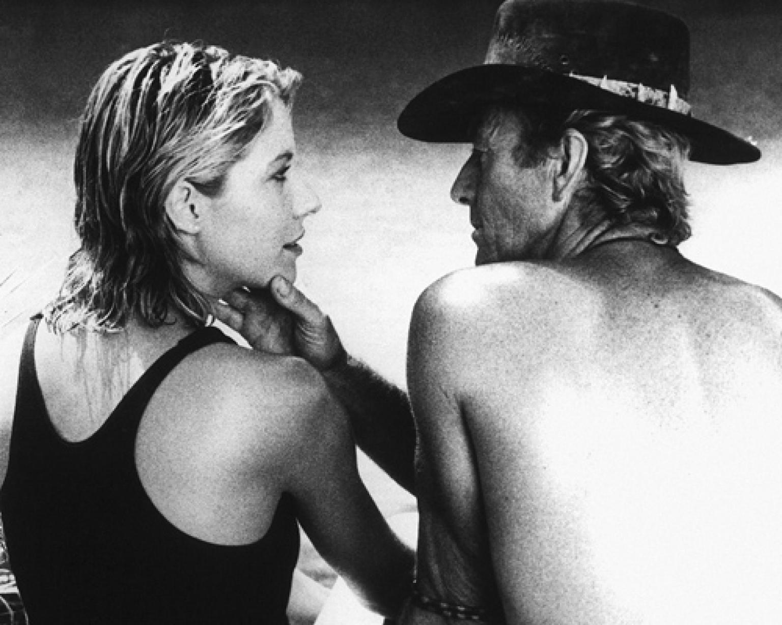 Linda Kozlowski as Sue Charlton and Paul Hogan as Mick 'Crocodile' Dundee sitting by a waterhole. He is touching her face and they are staring at each other.