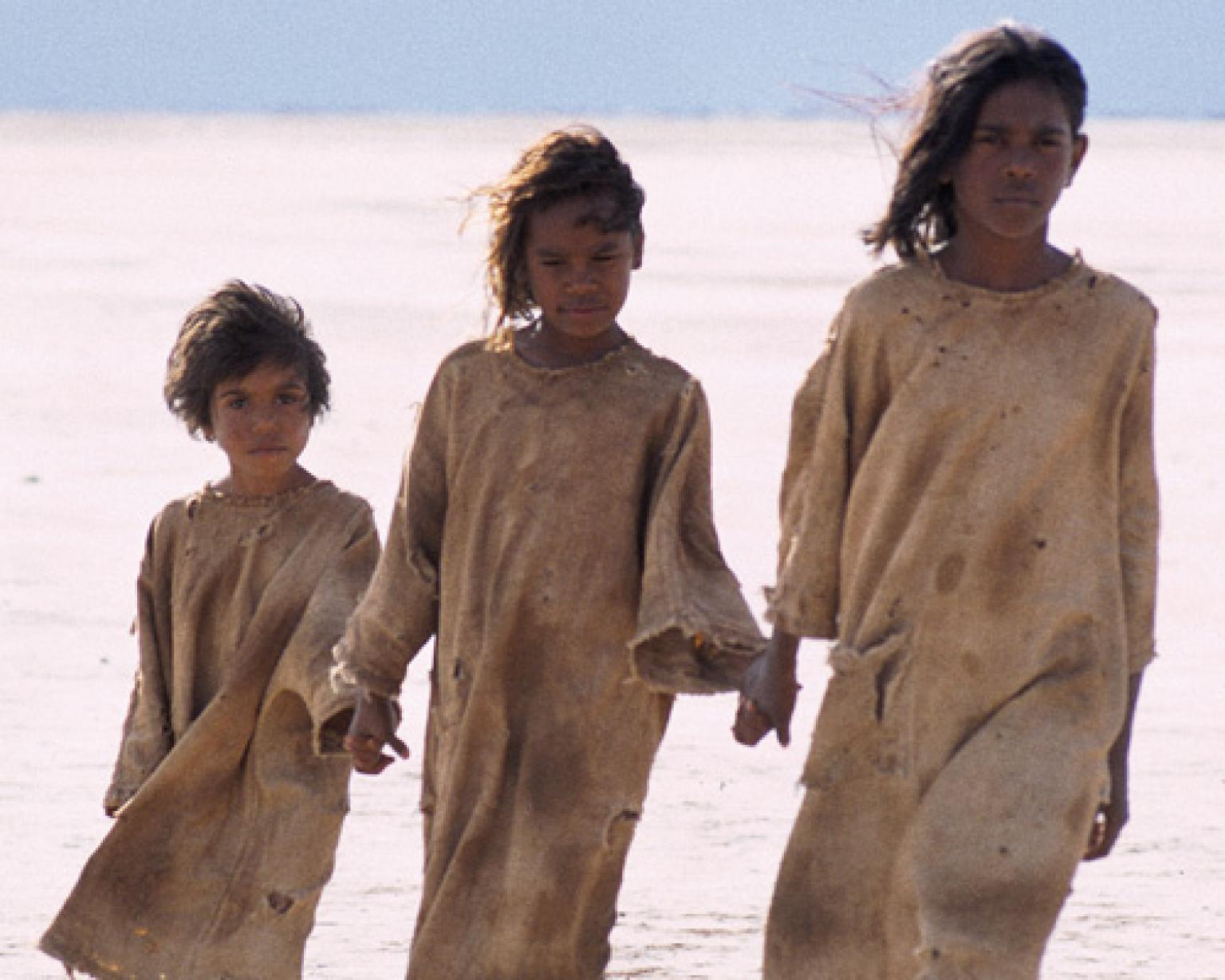 Tianna Sansbury as Daisy, Laura Monaghan as Gracie and Everlyn Sampi as Molly walking hand in hand across a salt flat.