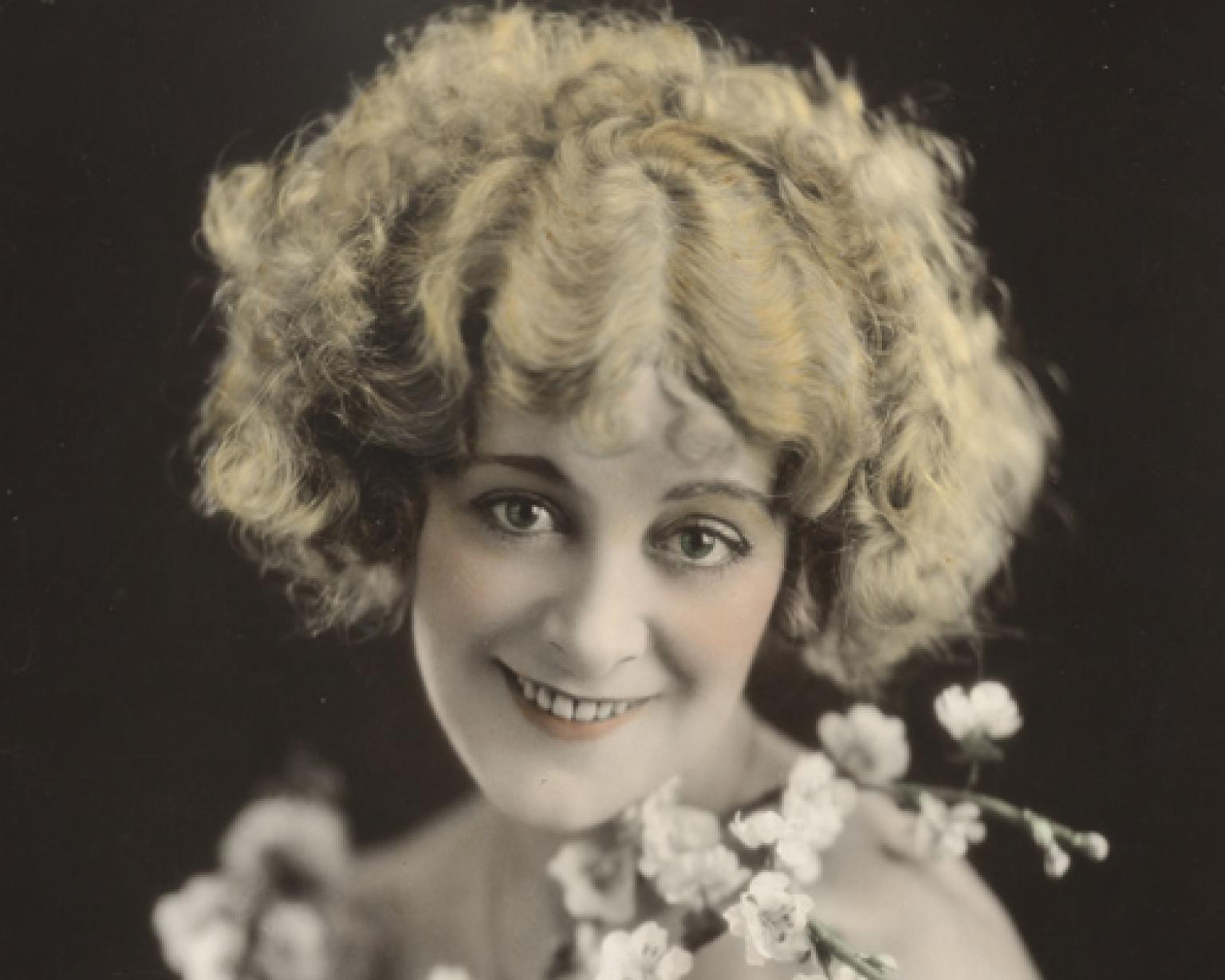 A hand-coloured publicity portrait of actor Vera James. Her face is bordered by cherry blossoms.