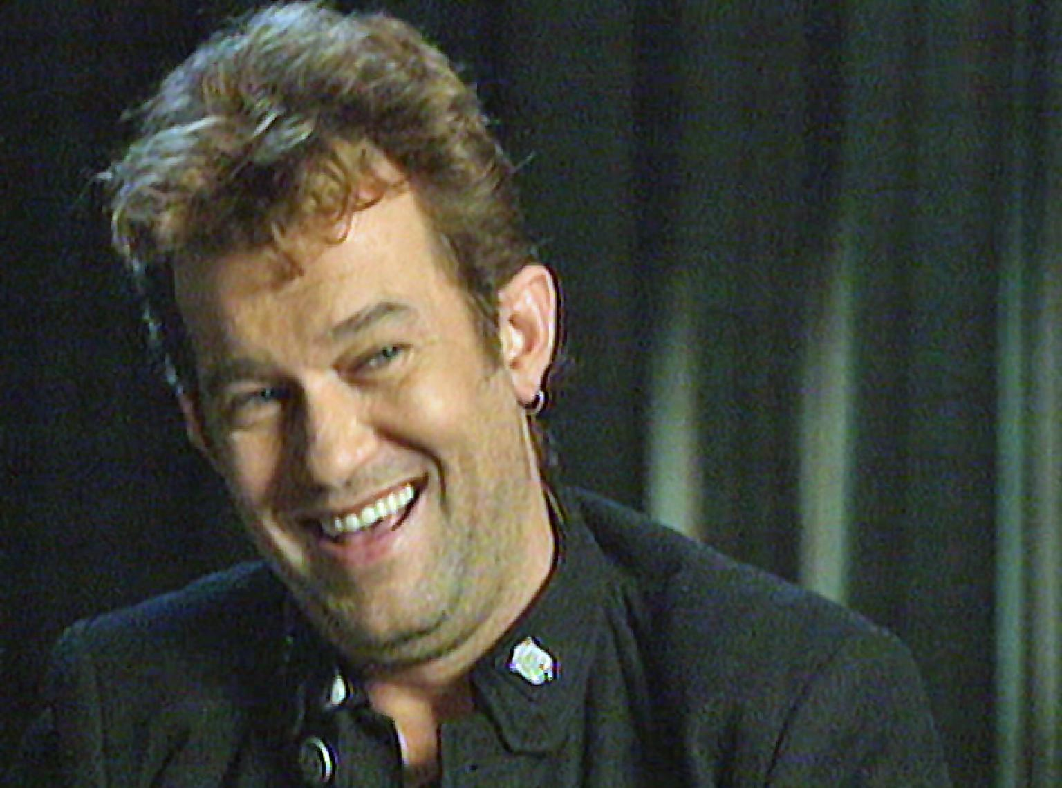 Close up head and shoulders shot of Jimmy Barnes wearing a black shirt and smiling at the camera with his head tilted slightly. There's a black curtain in the background.