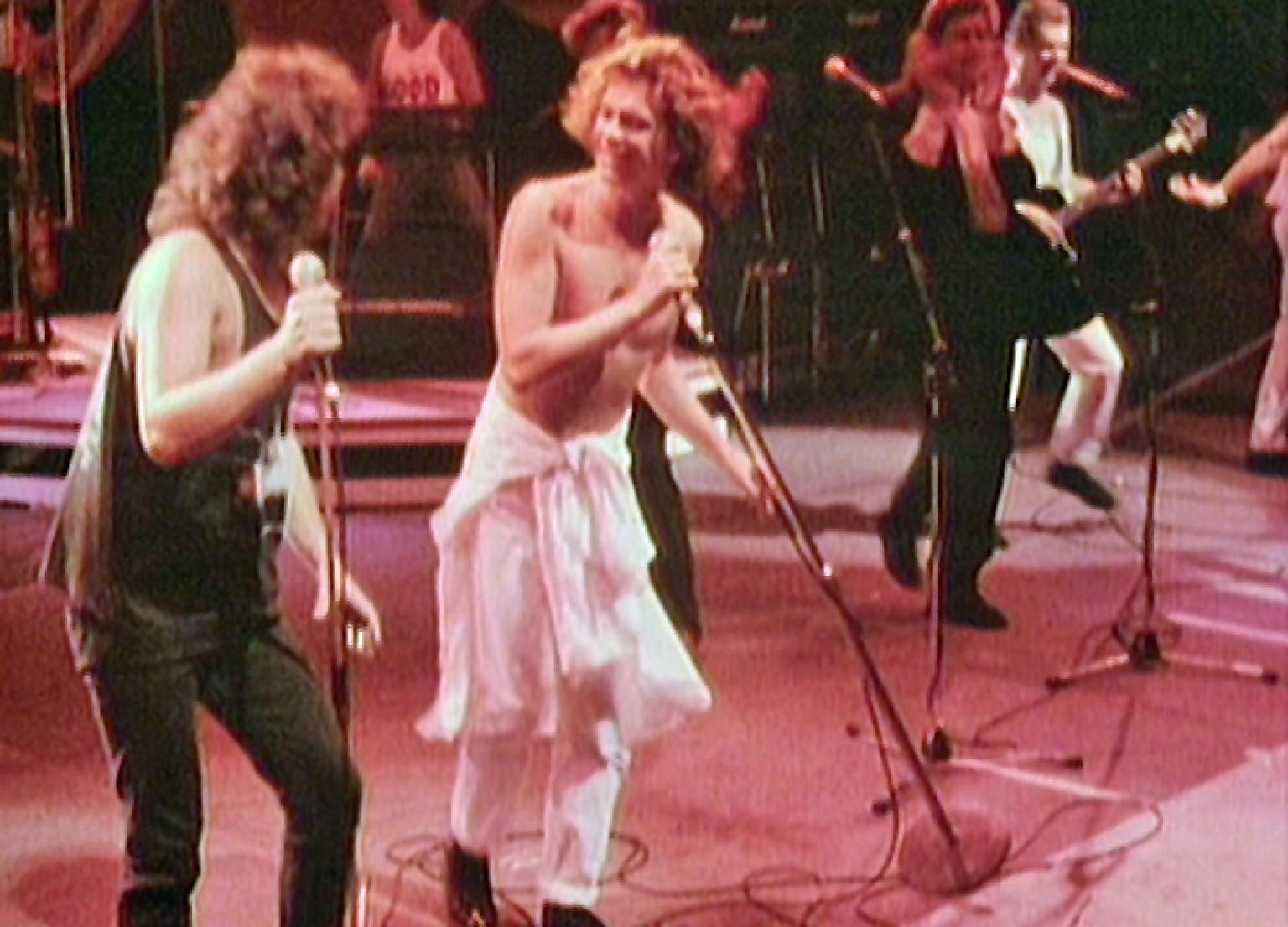 Jimmy Barnes and Michael Hutchence on stage at nighttime with lights at the back, Jimmy is dressed in black jeans and singlet and Michael is wearing white pants and no shirt. Both are singing into microphones.