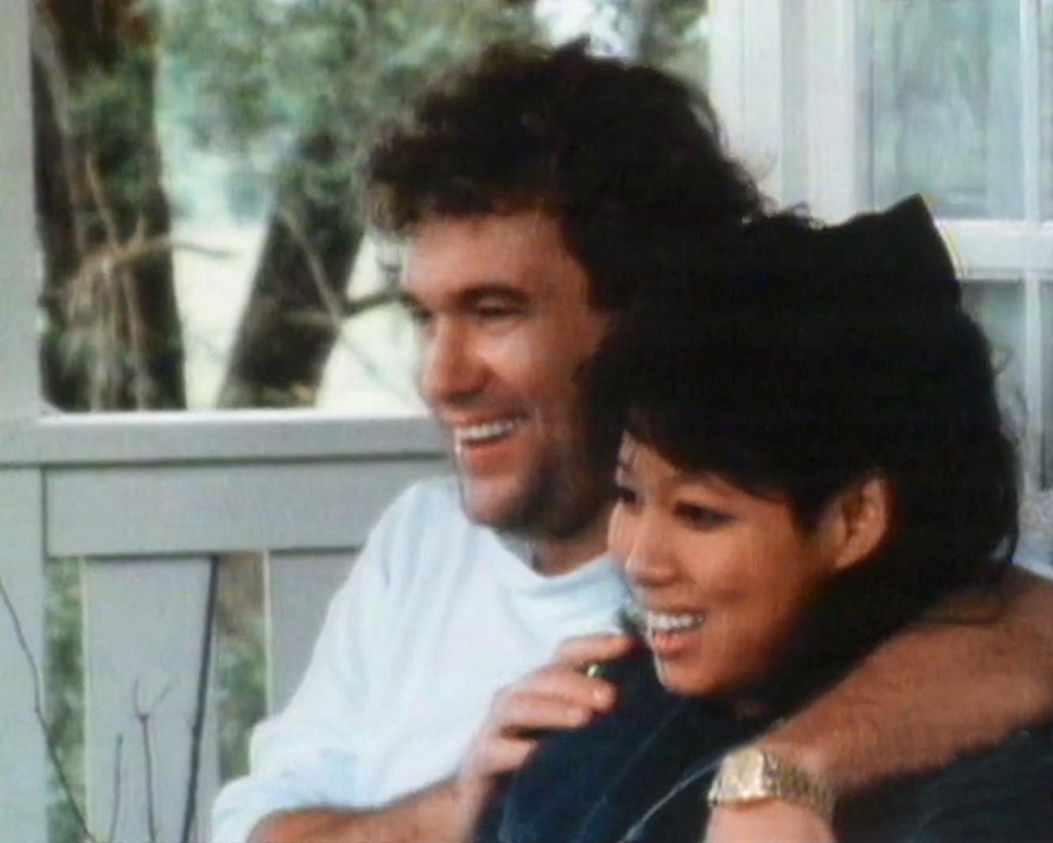 Jimmy Barnes, seated with his arm around his wife Jane. Both are smiling and facing to the left of screen. They appear to be seated outside on a front deck of a house.