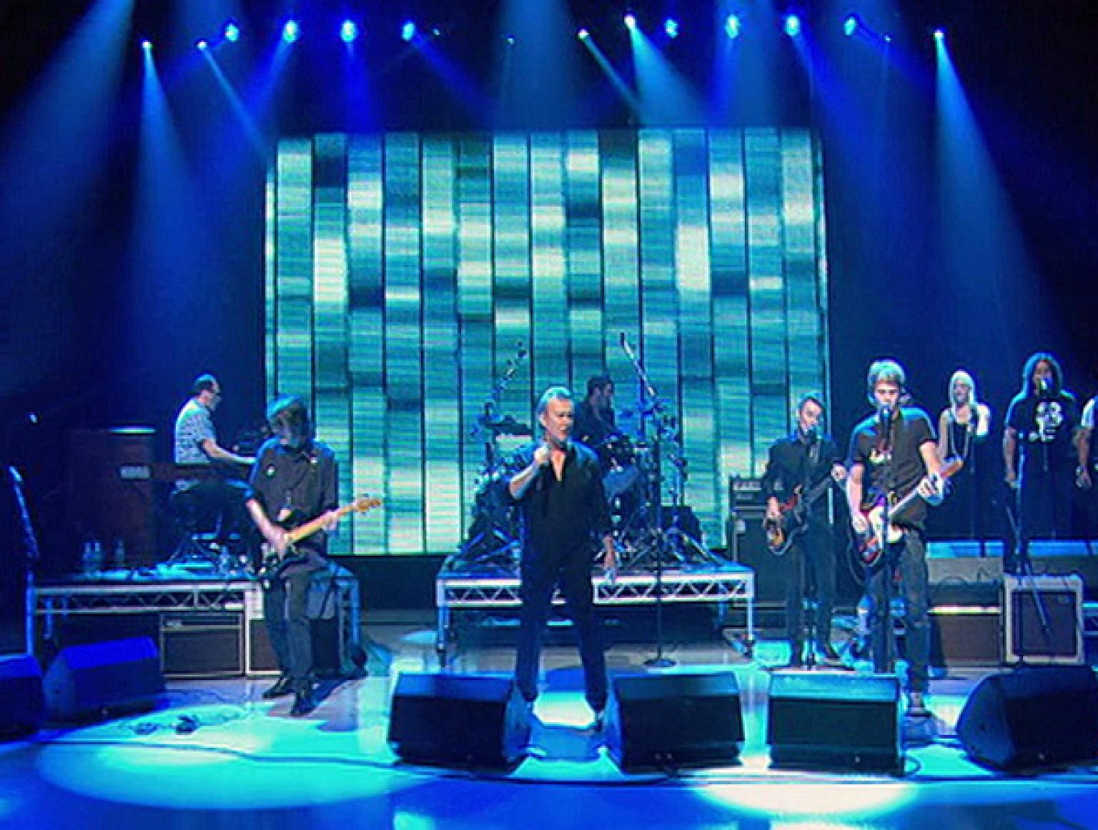 Wide shot of Jimmy Barnes (centre) on a TV studio stage surrounded by band members. The TV studio is flooded in different shades of blue lights. Barnes is dressed all in black and holding a microphone.