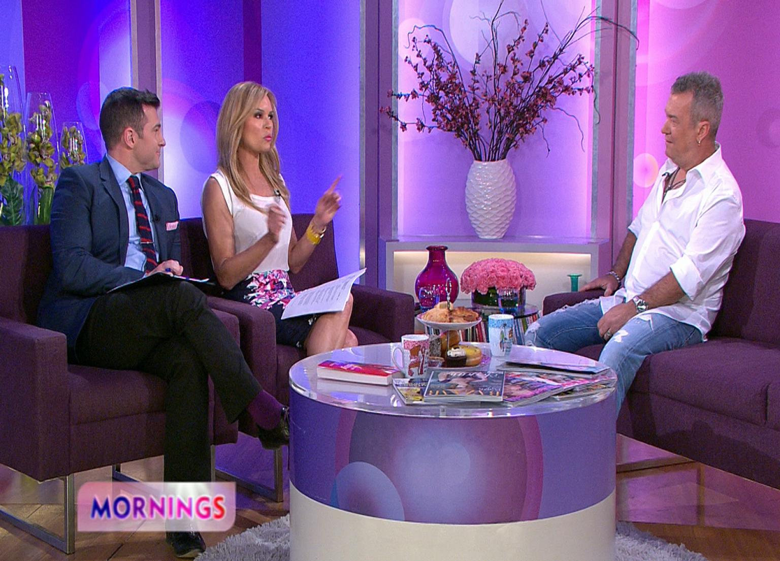 Studio seting with pink and purple background. TV show hosts David Campbell and Sonia Kruger sit on the left in chairs. Jimmy Barnes is on the right on a couch. A round coffee table is in front and vases of various shapes and sizes are in the background.