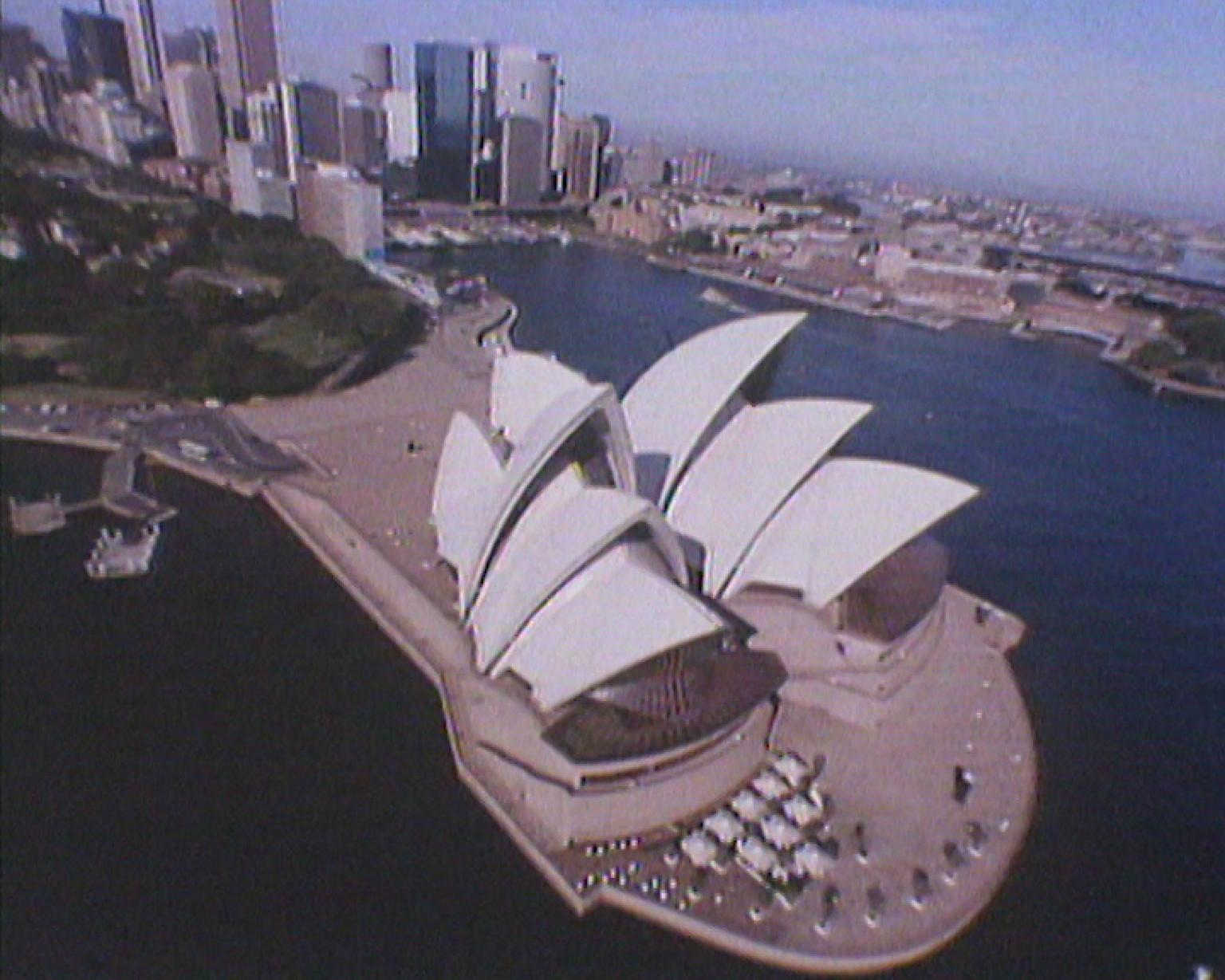Overhead shot of the Sydney Opera House, with Circular Quay and the city in the background.