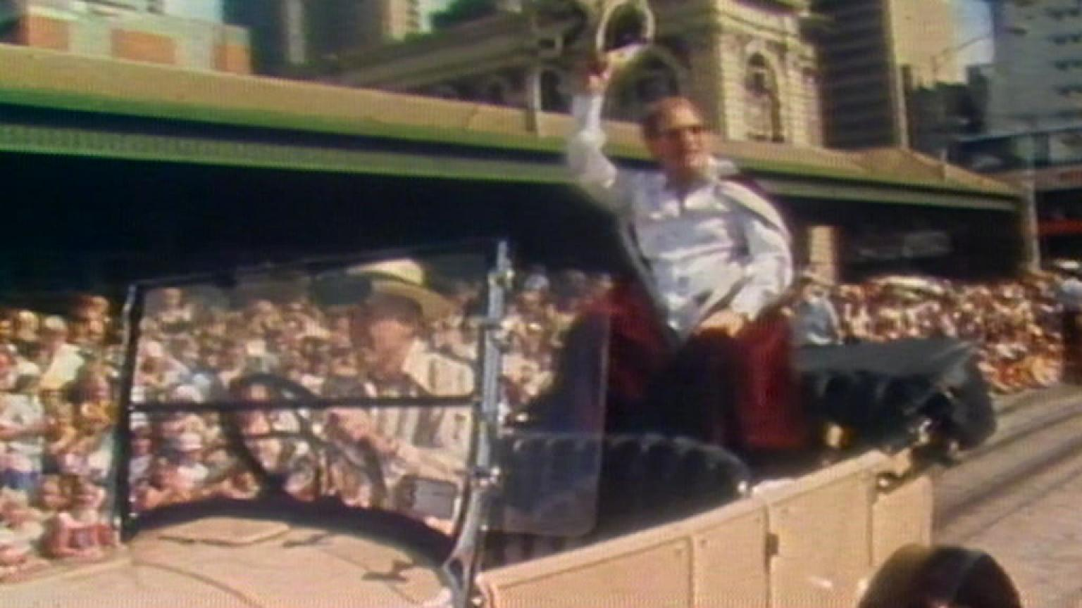 Graham Kennedy in the back of a convertible waving to the crowds as King of Moomba