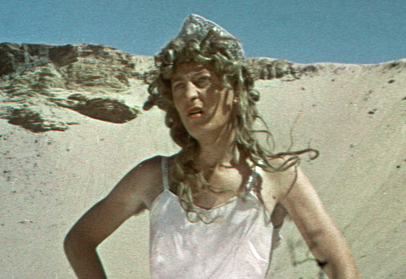 Graham Kennedy in a long blonde wig and dress standing in the desert