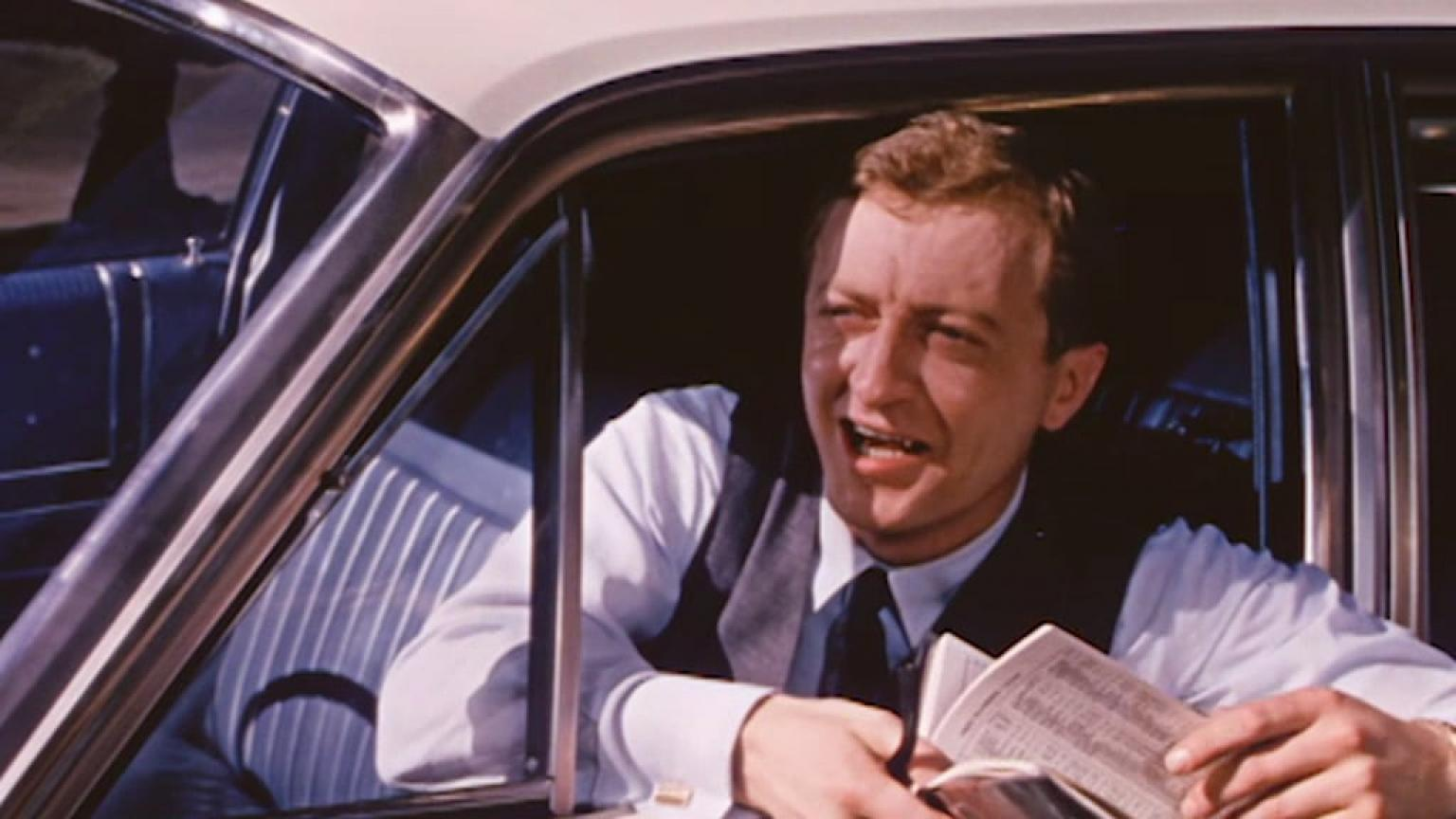 Graham Kennedy leaning out of a car window asking for directions