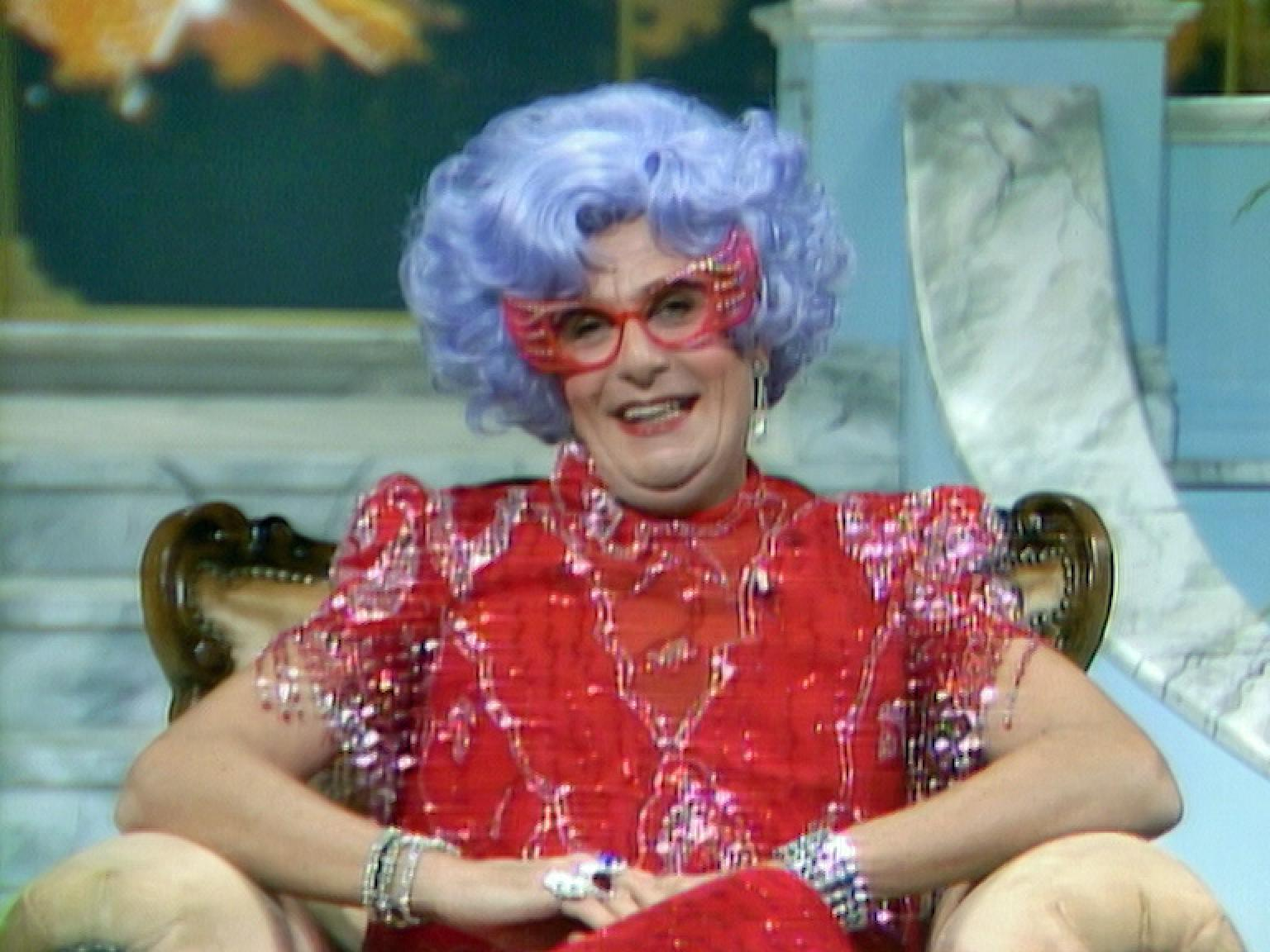 Dame Edna has a confiding look as she looks at the camera.