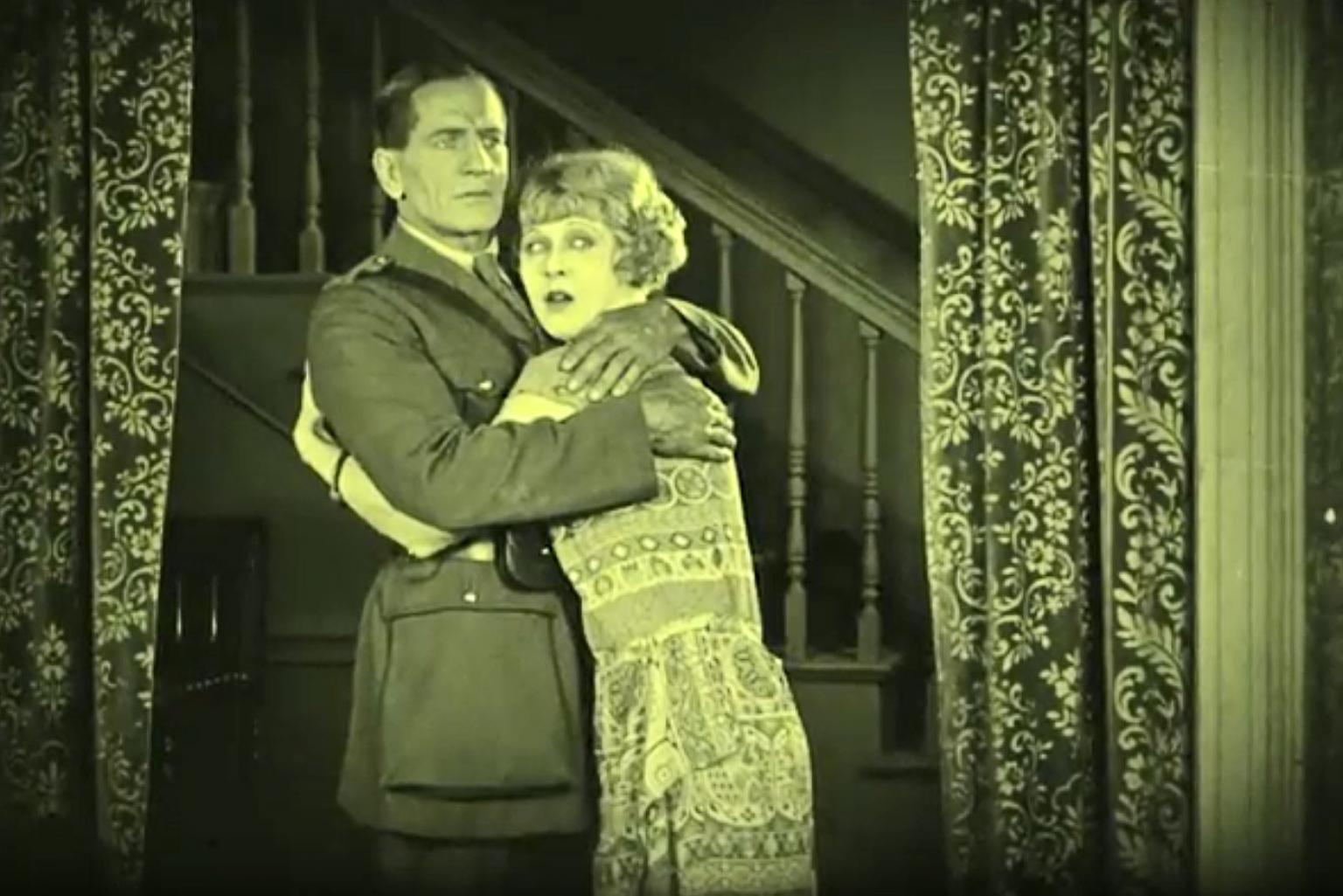 A couple embrace in front of a staircase with curtains on either side. They both have concerned looks on their faces. The image is from a scene in the silent era film Empire Builders (1924).