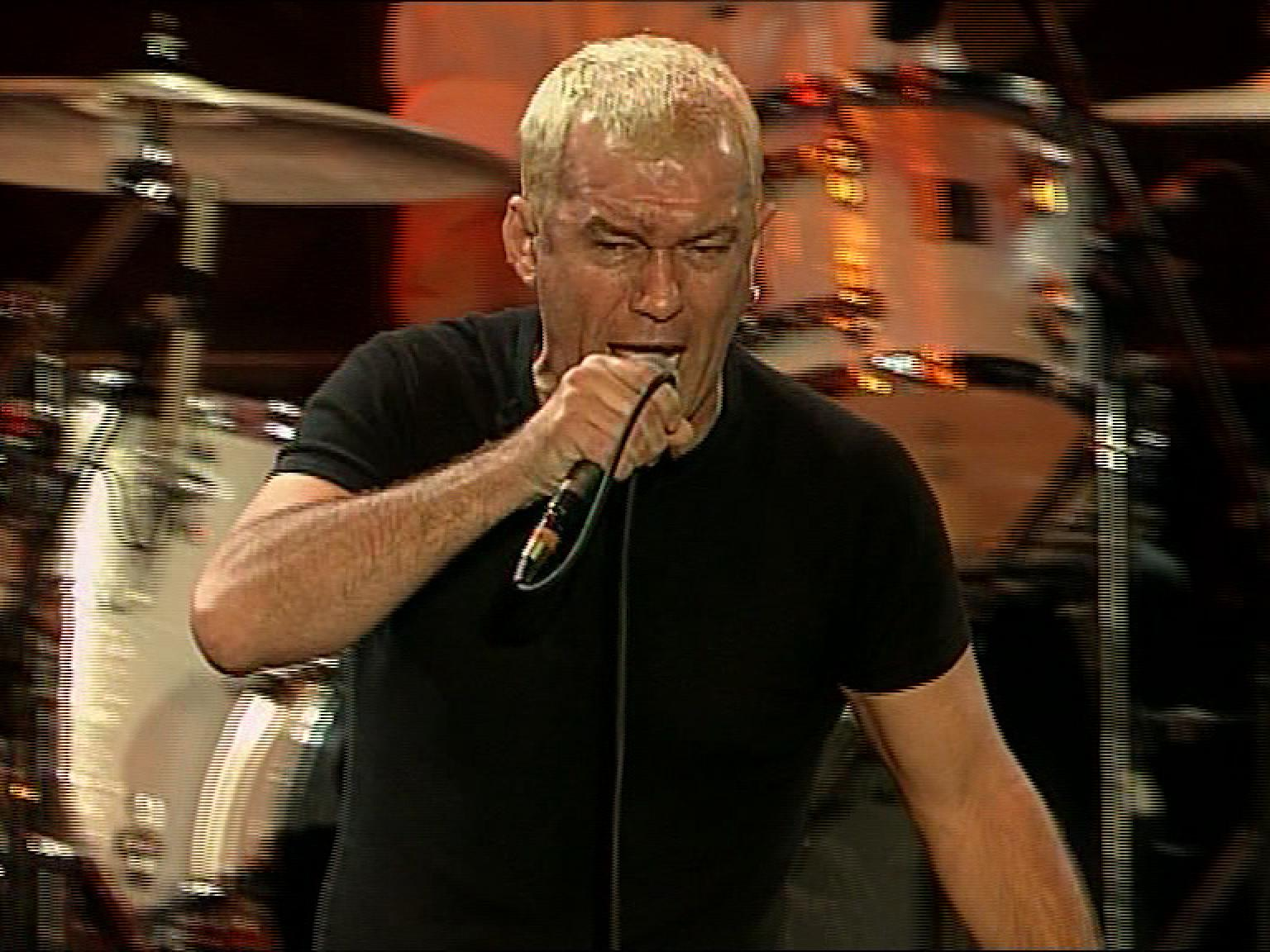 Jimmy Barnes wearing black t-shirt on stage, singing into a microphone. He is pictured from the waist up with a drum kit in the background.