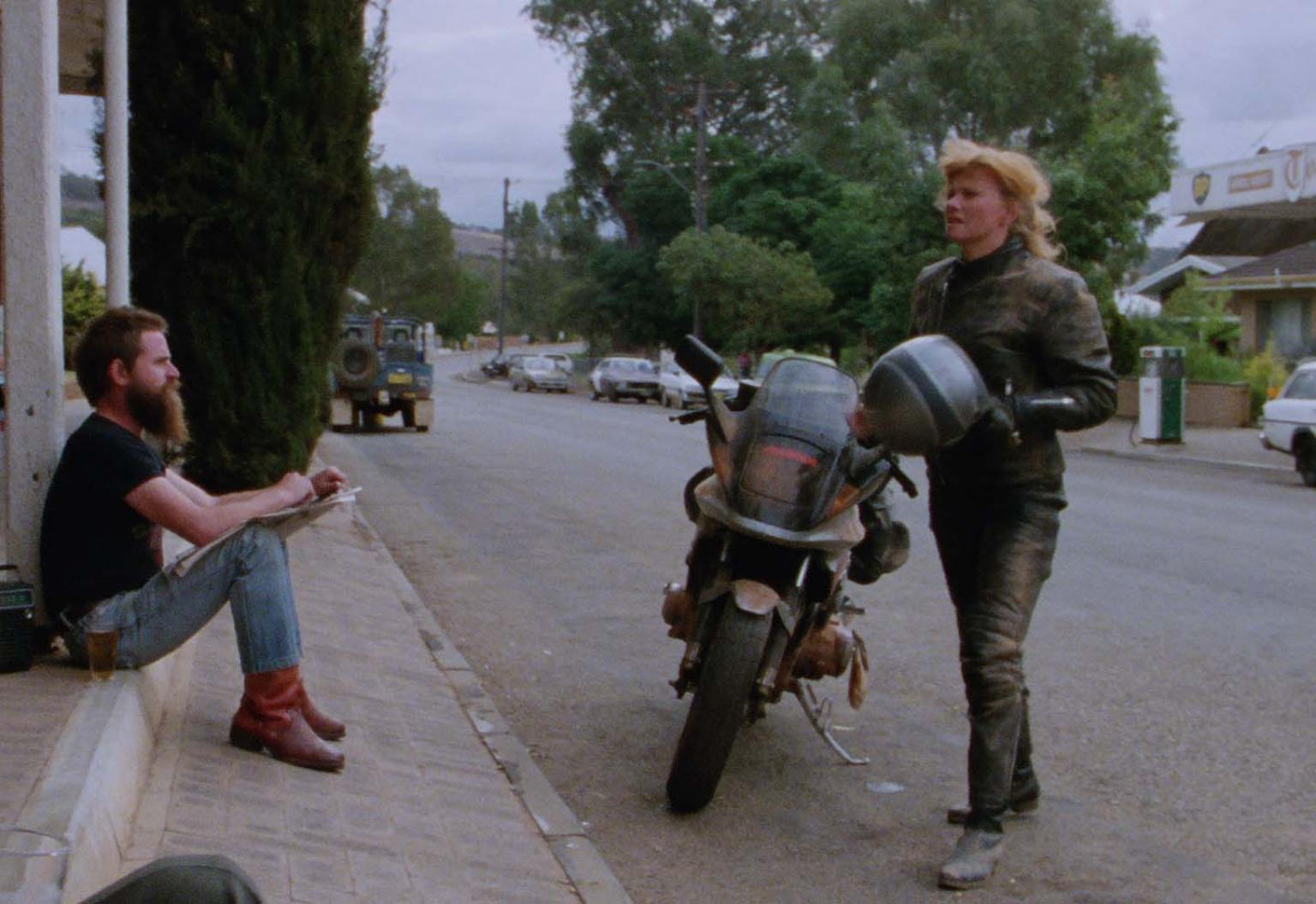 Deborra-lee Furness has dismounted her motorcycle outside a country pub in a still from the film Shame