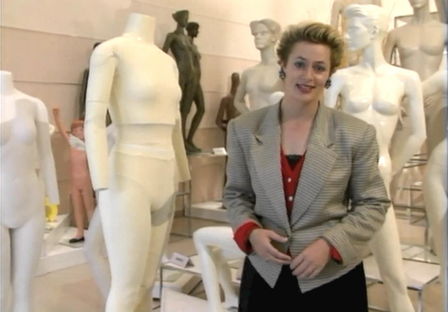 Amanda Keller stands in front a group of mannequins. The mannequins are in various states of undress.