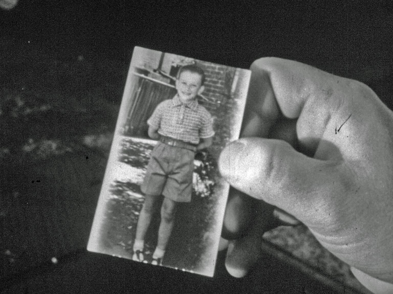 A close up of a man's hand holding a small photograph of a young boy. The boy in the photograph is wearing a shirt and shorts and is smiling directly at the camera.