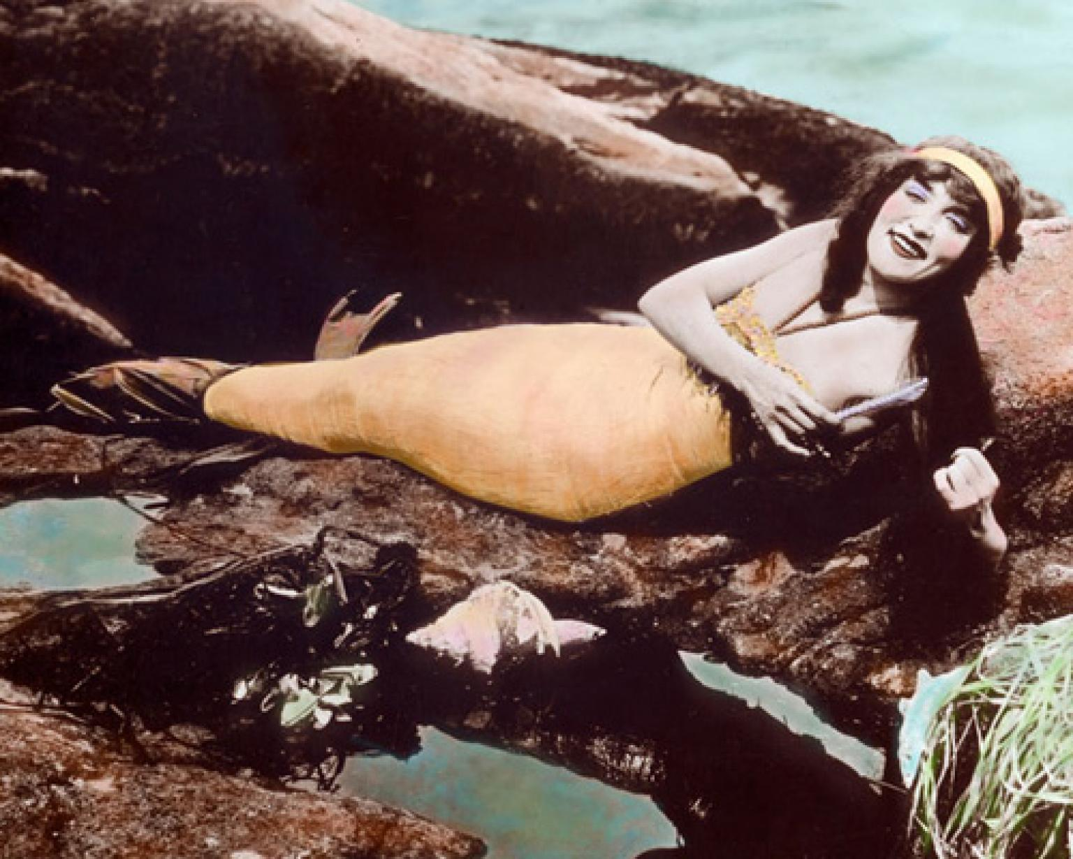 A hand-tinted photograph of Annette Kellerman wearing a mermaid costume and lying on rocks near the water.