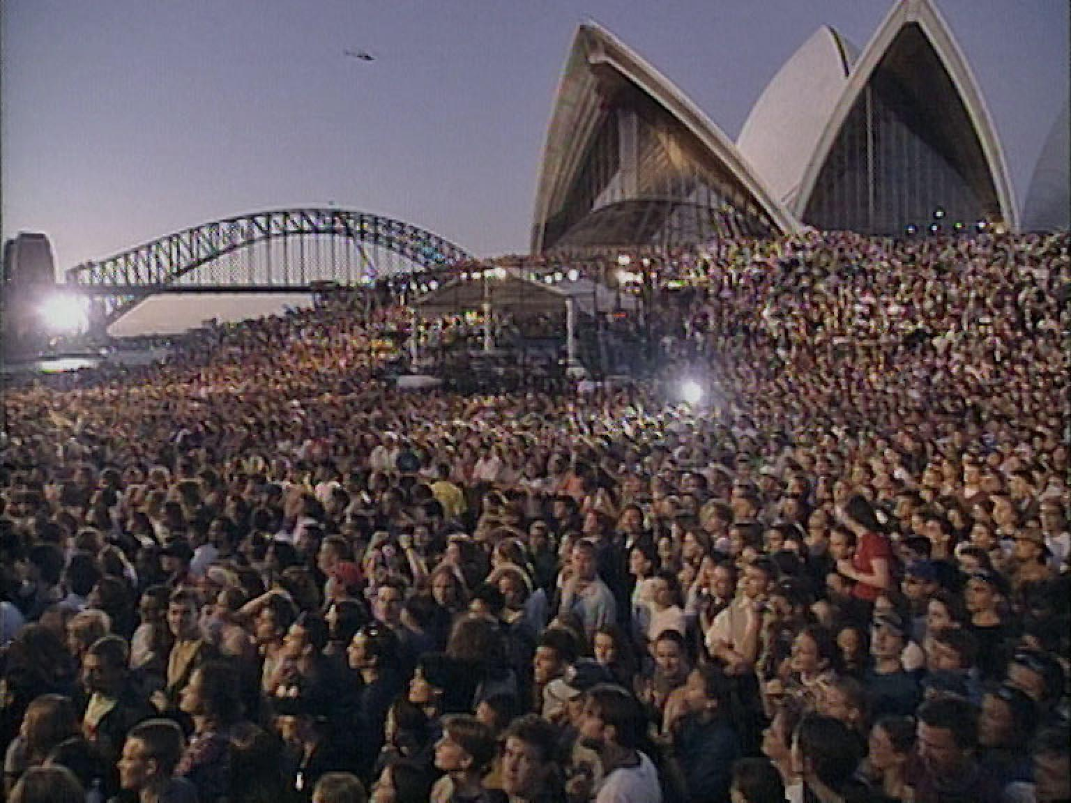 A sea of people cover the forecourt steps of the Opera House. The Sydney Opera House sails and the Sydney Harbour Bridge are in the background.