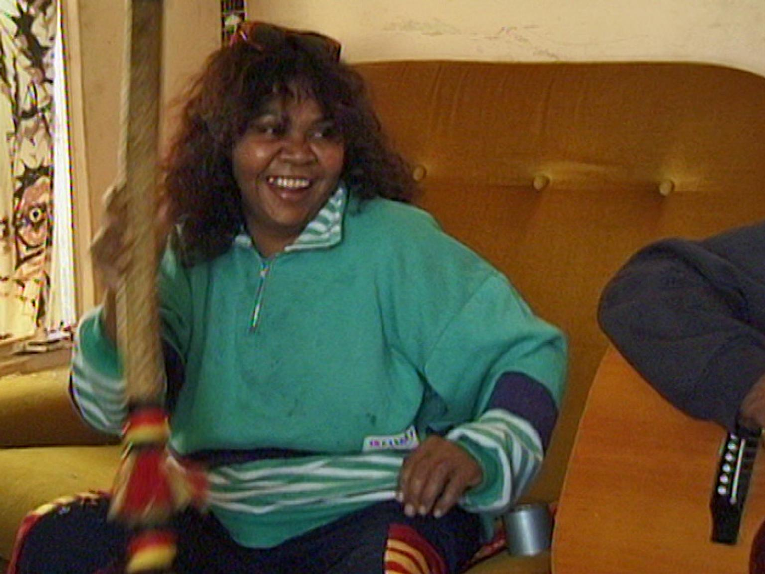 Ruby Hunter sitting on a sofa and smiling. She's holding an Aboriginal musical instrument.
