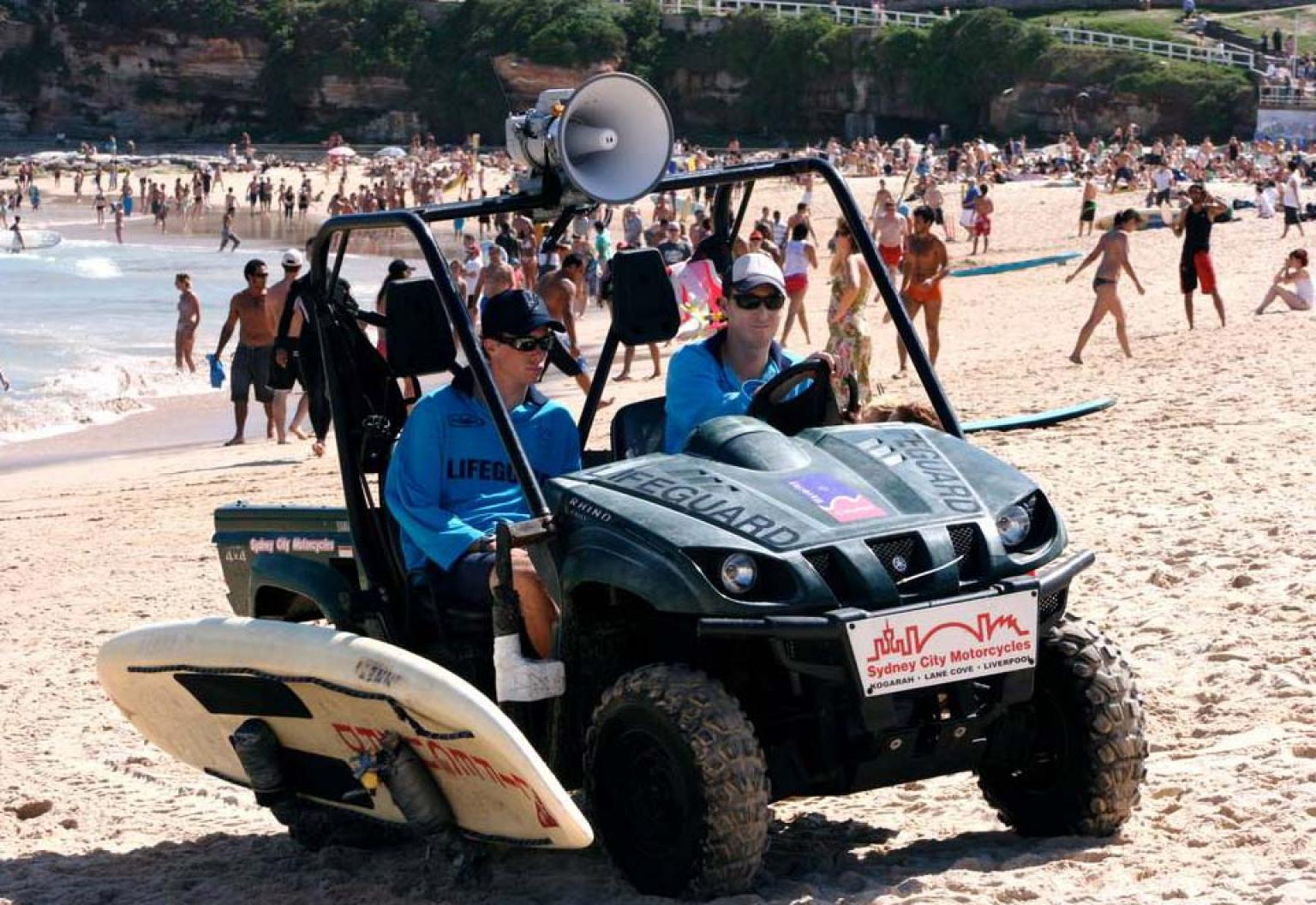 Two lifesavers driving a buggy on a crowded Bondi Beach in a scene from Bondi Rescue