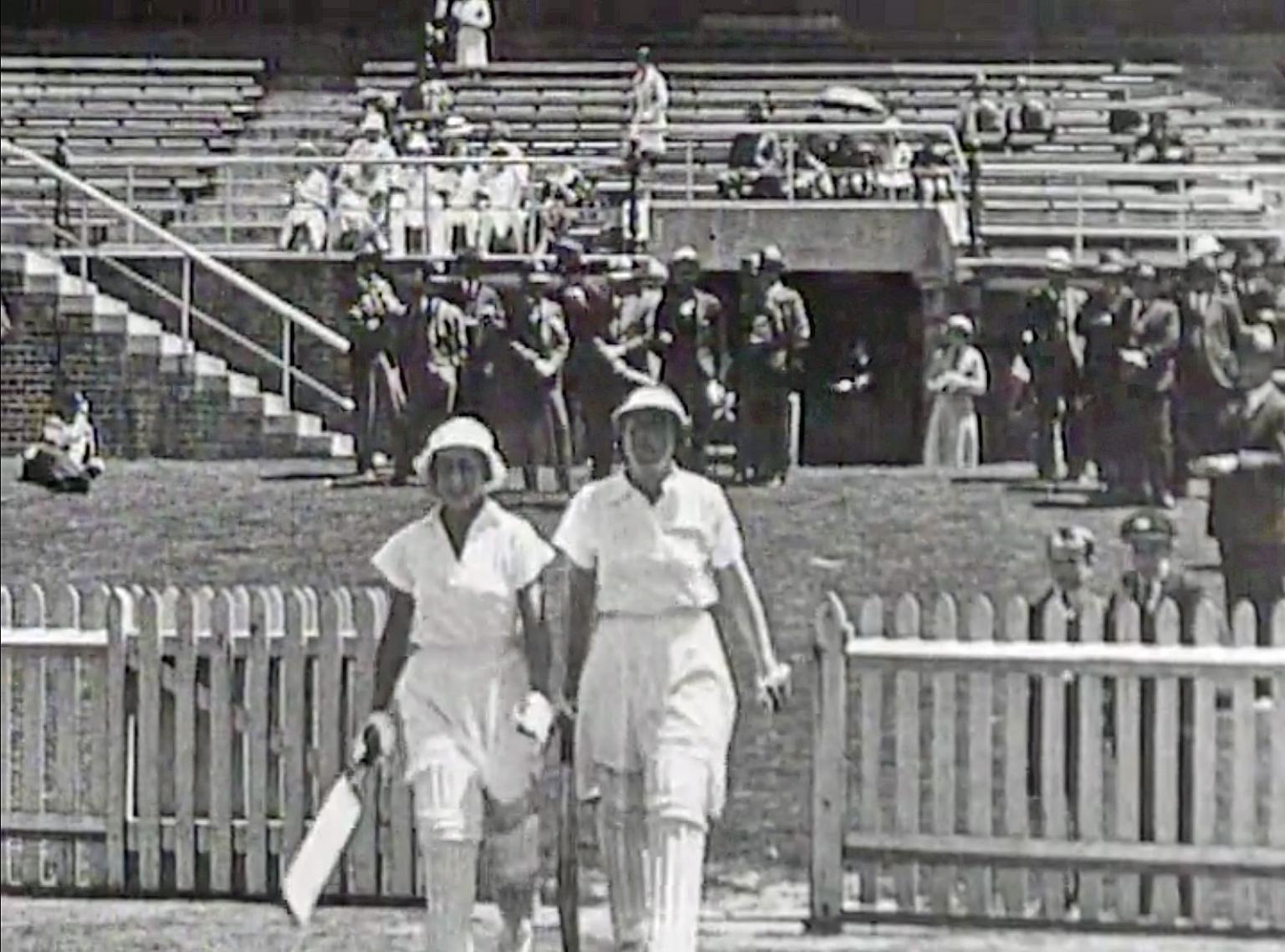 Two women cricketers walking onto a cricket pitch, they are wearing white uniforms and protective leg pads and holding cricket bats.