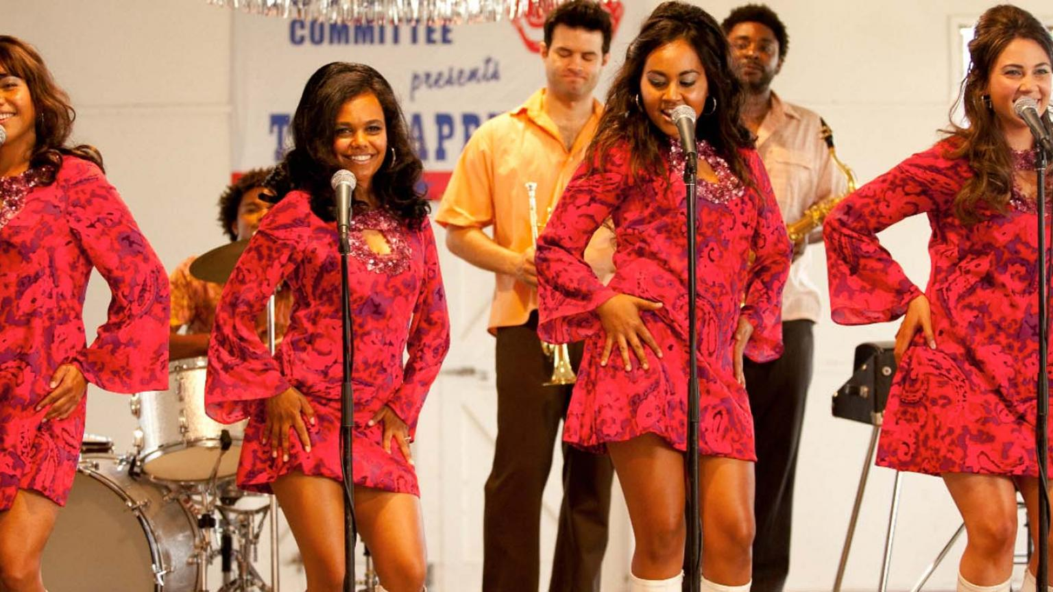 The four members of the Indigenous singing group The Sapphires perform on stage in colourful red dresses in a re-creation of a 1960s concert in the film The Sapphires