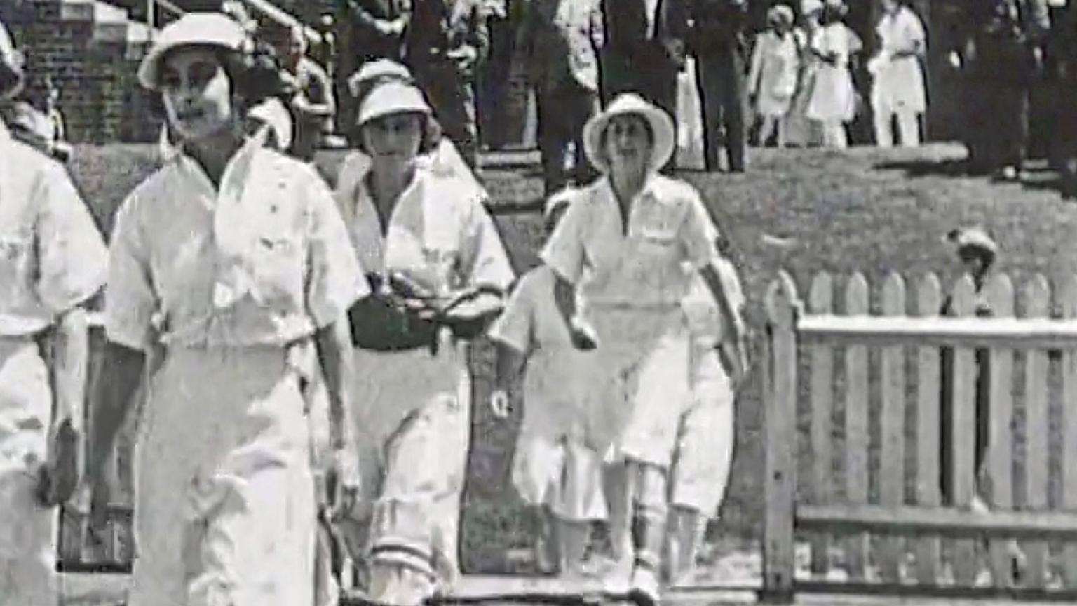 A team of women cricketers from the 1930s walking onto a cricket field in white uniforms.