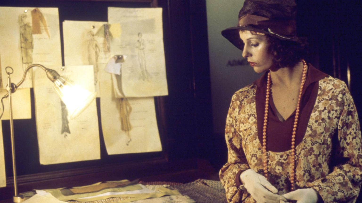 Film still of Helen Morse as Caddie looking at drawings of women's dress designs in a studio.