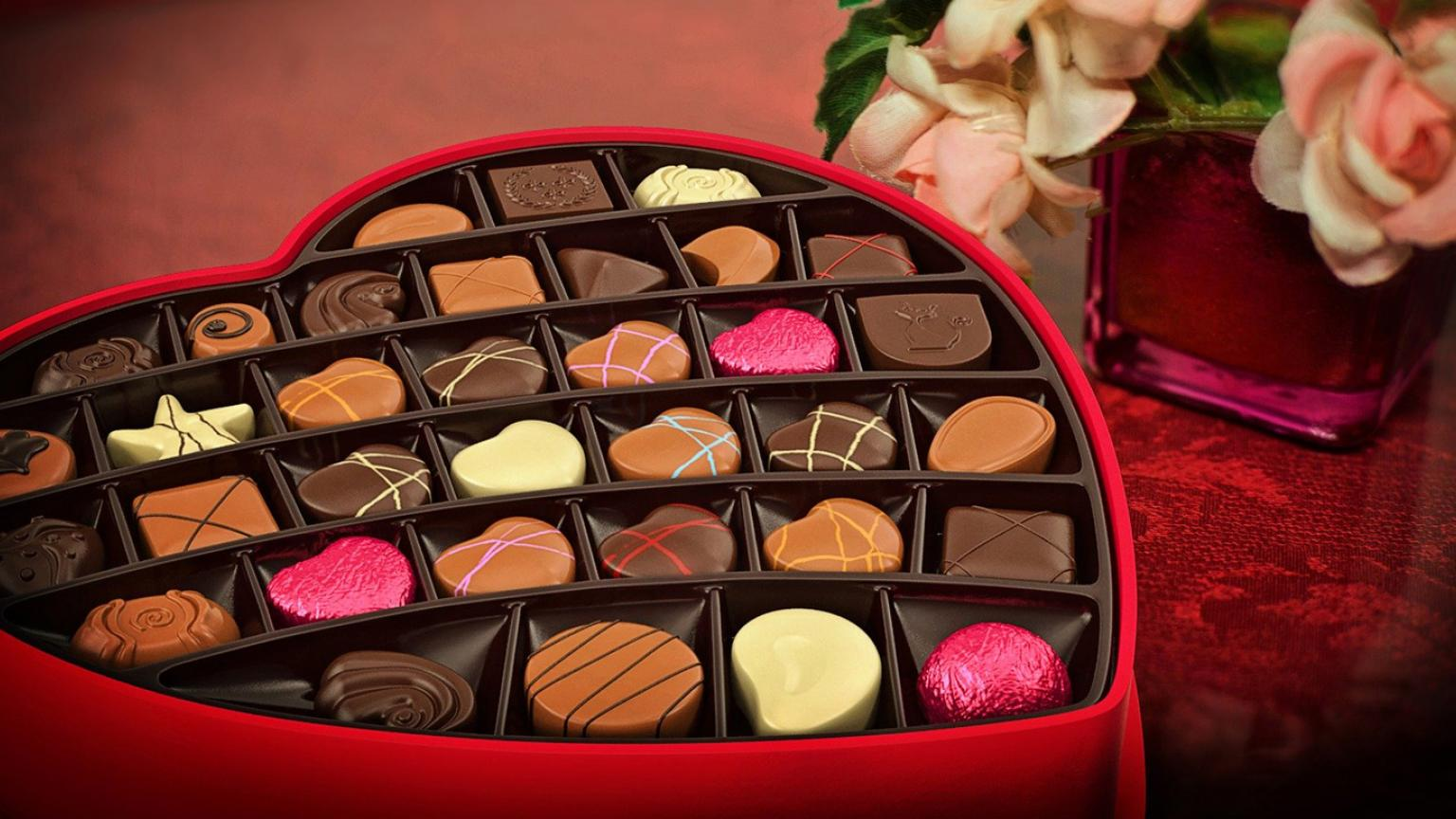 A heart shaped box of assorted chocolates with a small vase of pink roses in the background