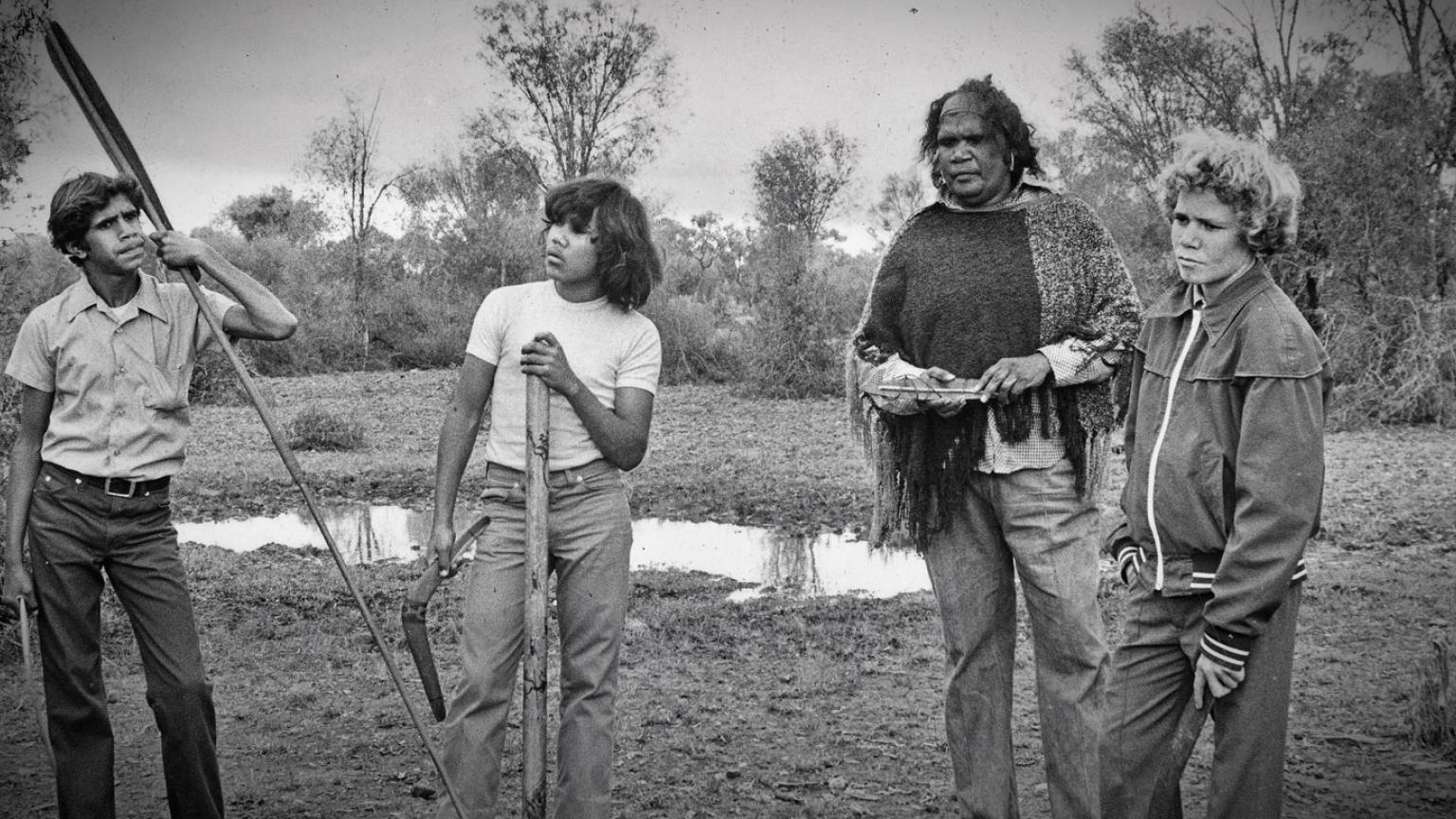 Four Aboriginal males stand in a bush setting wearing casual clothes and carrying traditional hunting tools.