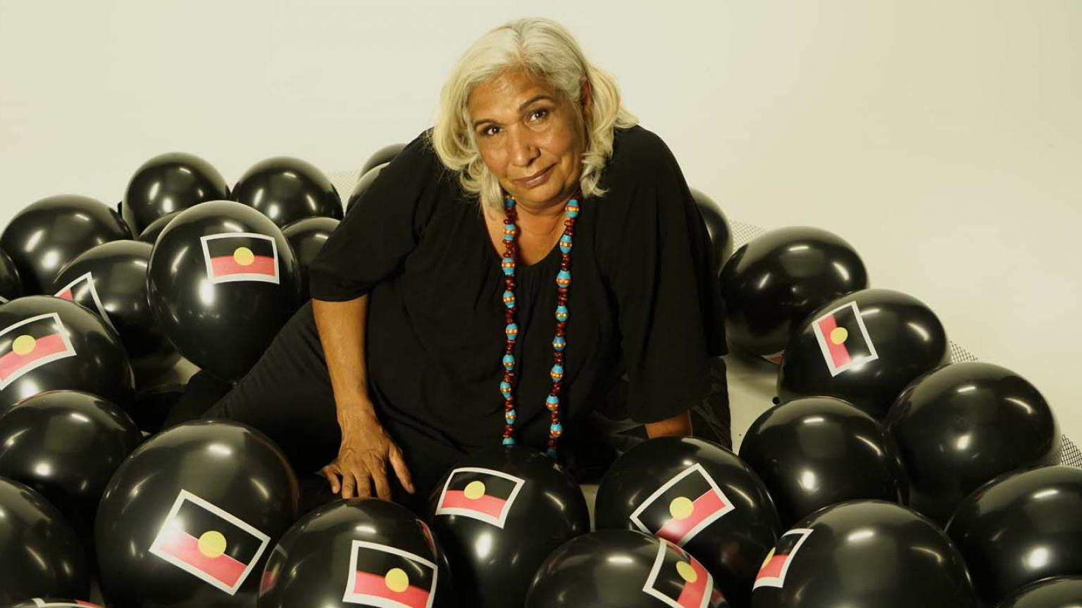 Trisha Morton-Thomas wearing a black dress and surrounded by black balloons with the Aboriginal flag on them