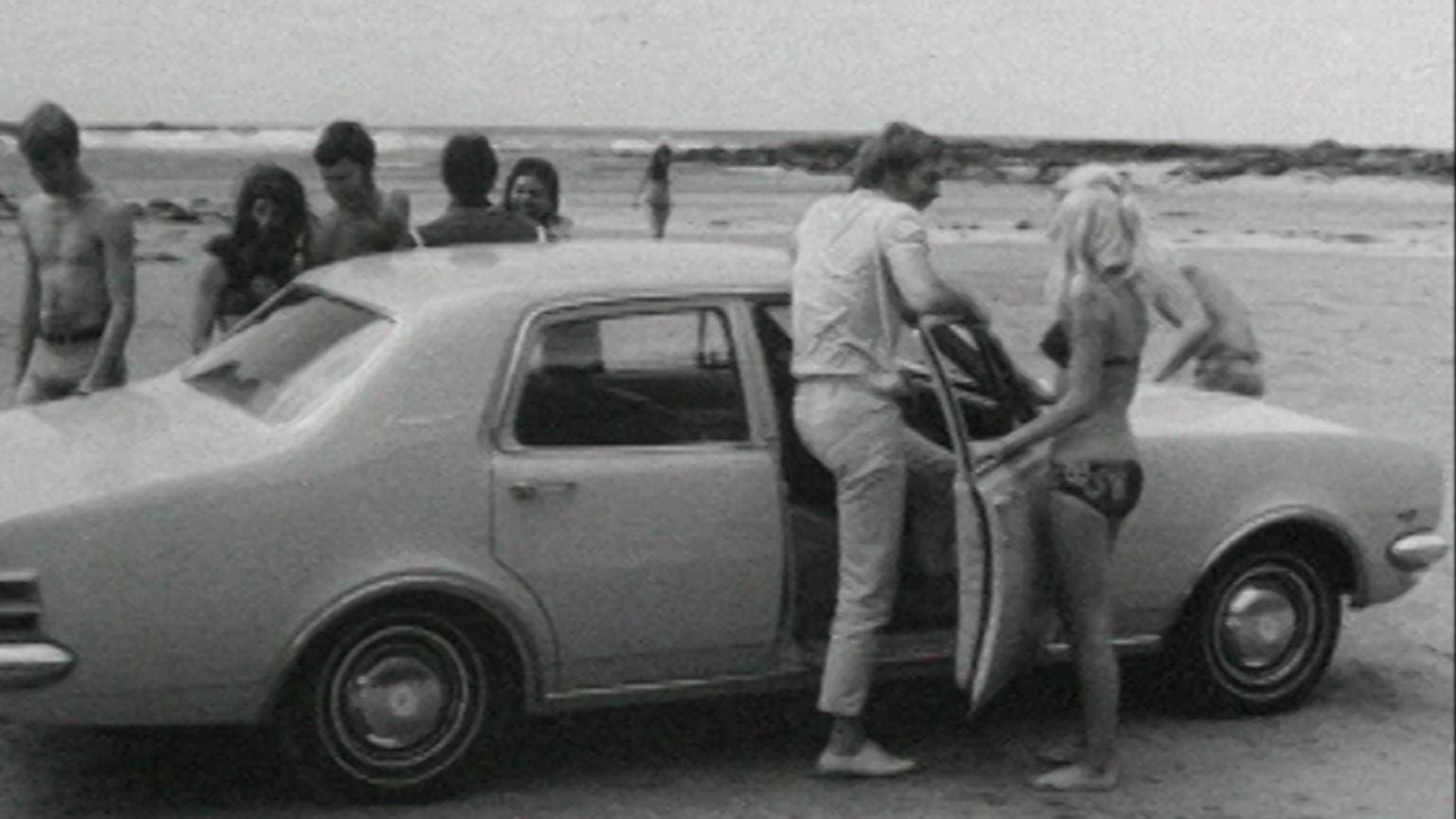 A group of young people stand around a Holden car on a beach