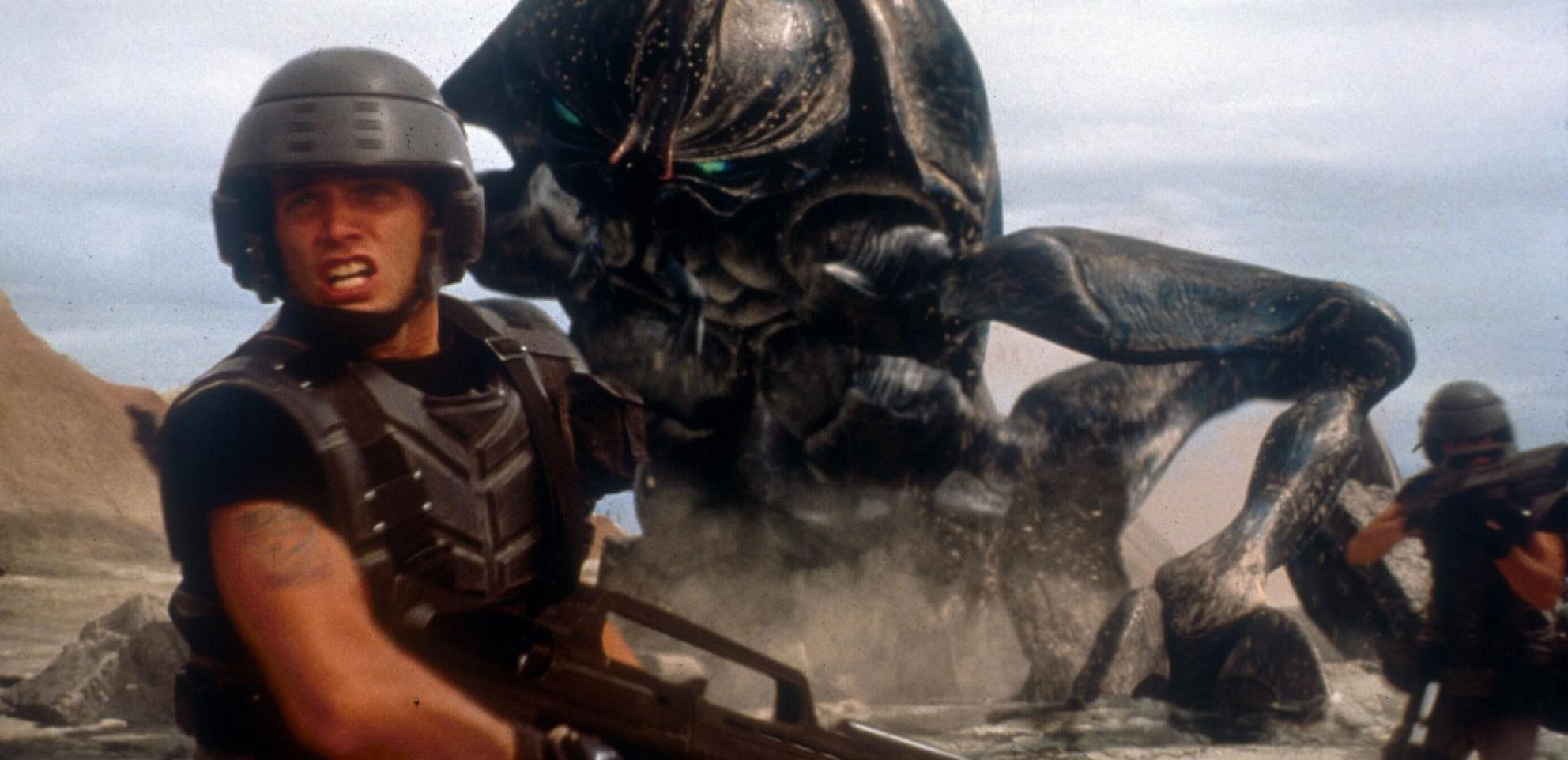 A soldier turns to run away from a giant attacking insect
