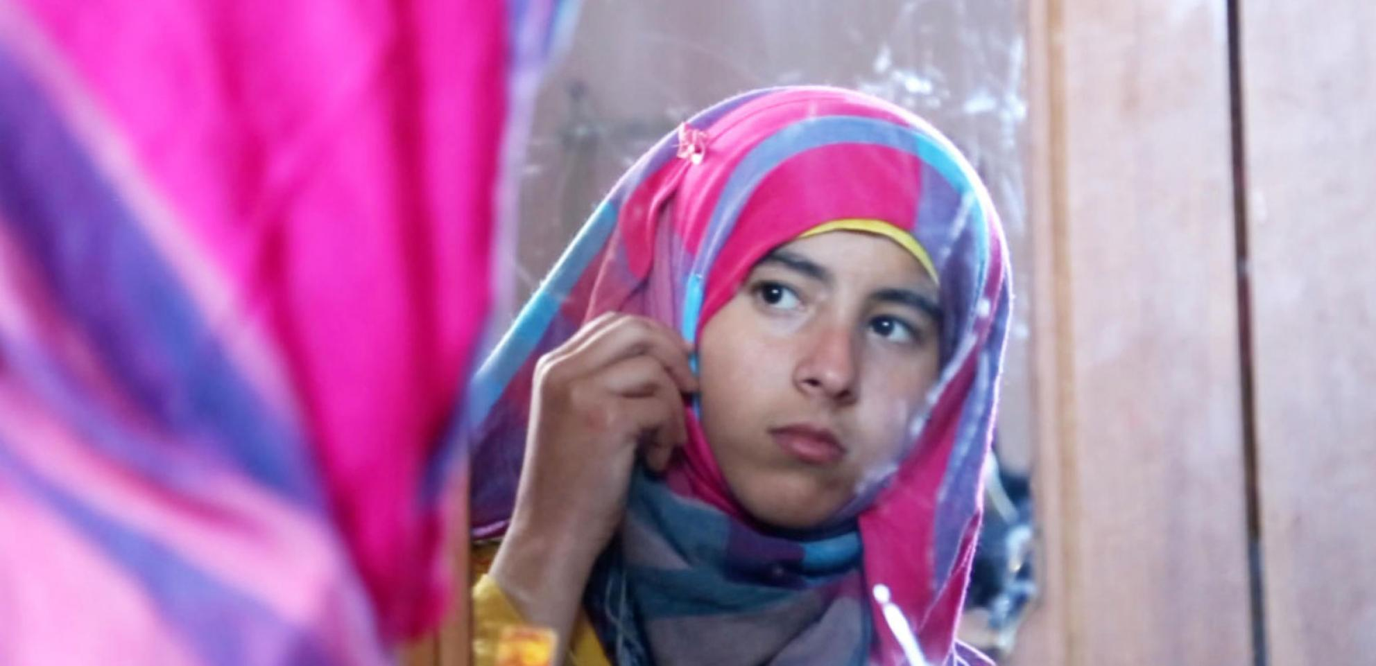 A young Muslim girl looks at herself in the mirror.